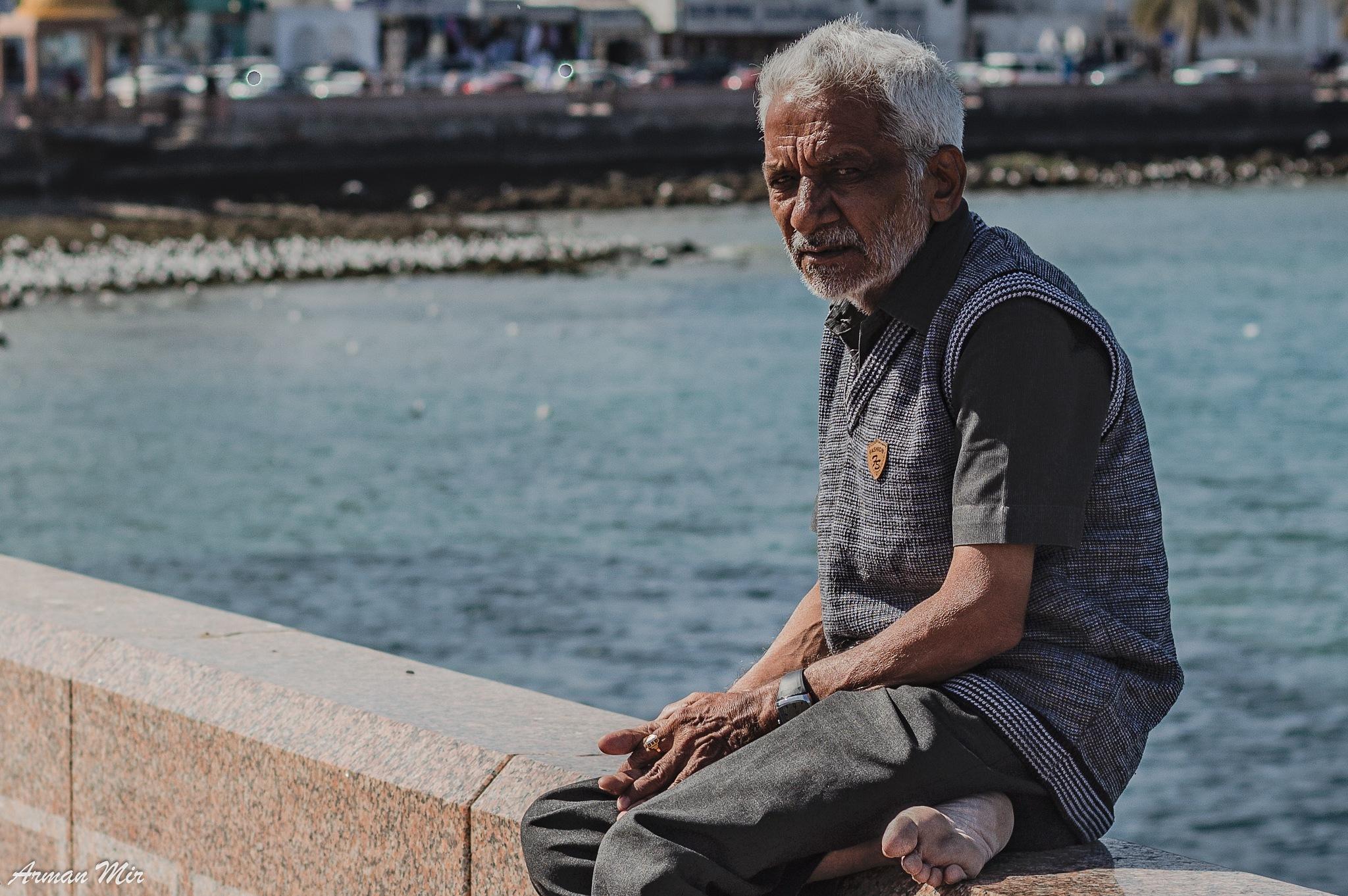 Photo in People #oman #muscat #port #bay #bock #sitting #elderly #pops #old man #elderly man #sea #water #portrait #street photography #travel #vacation #arab #omani #coast #holiday