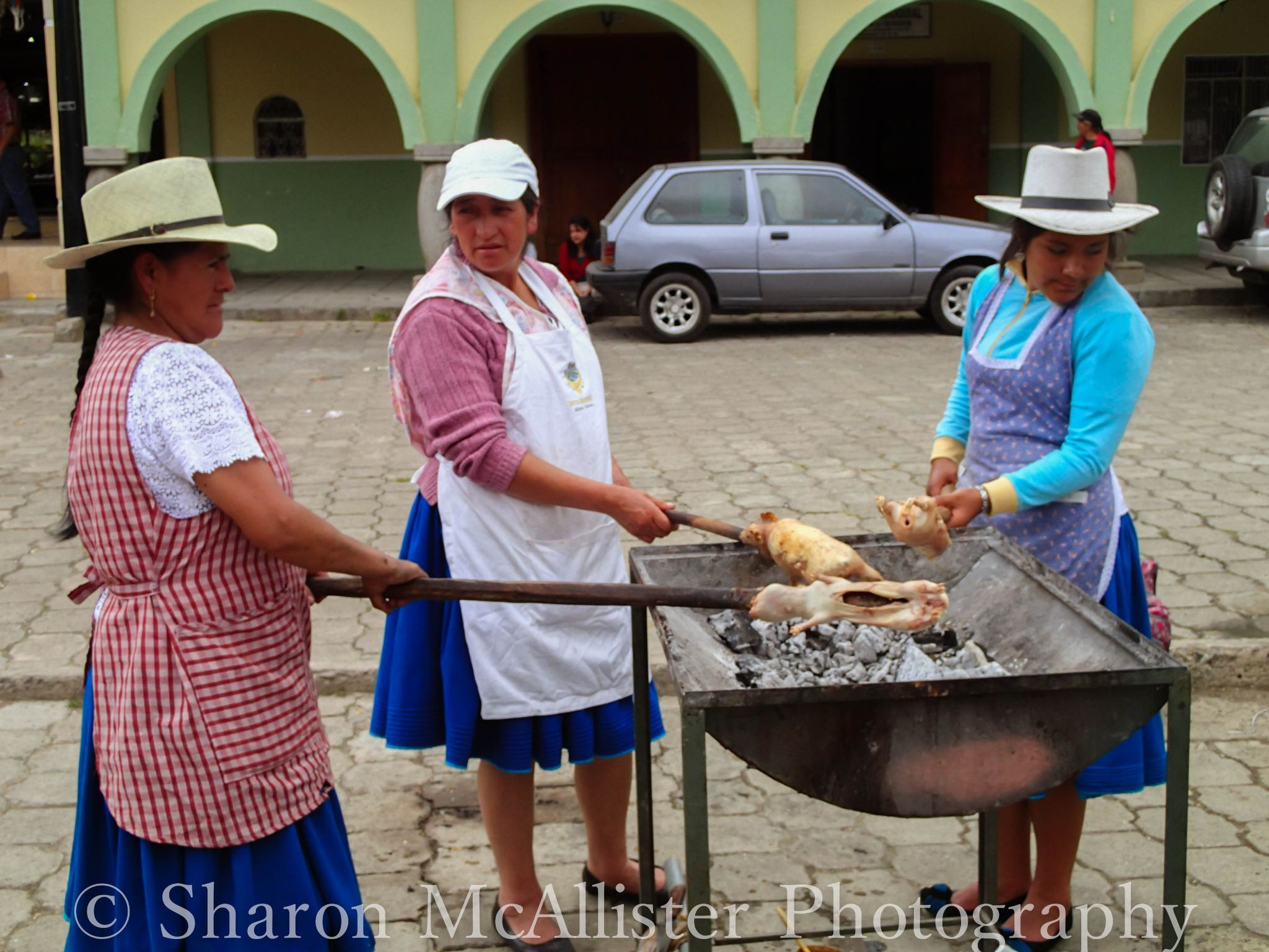 Ecuadorian Women spit roasting guinea pigs to sell which is the local delicacy by Sharon McAllister