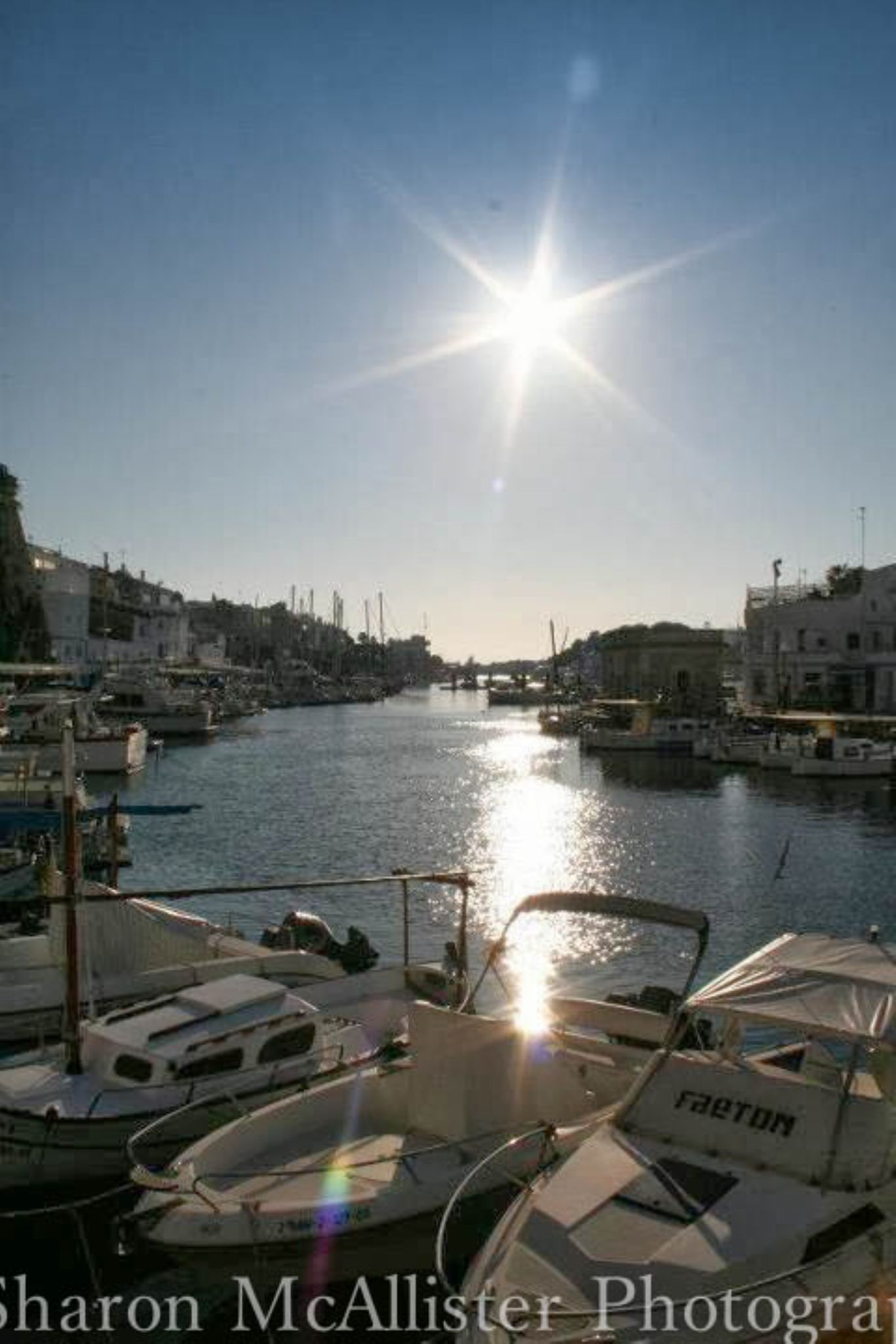 Sunset over boats in Menorca by Sharon McAllister