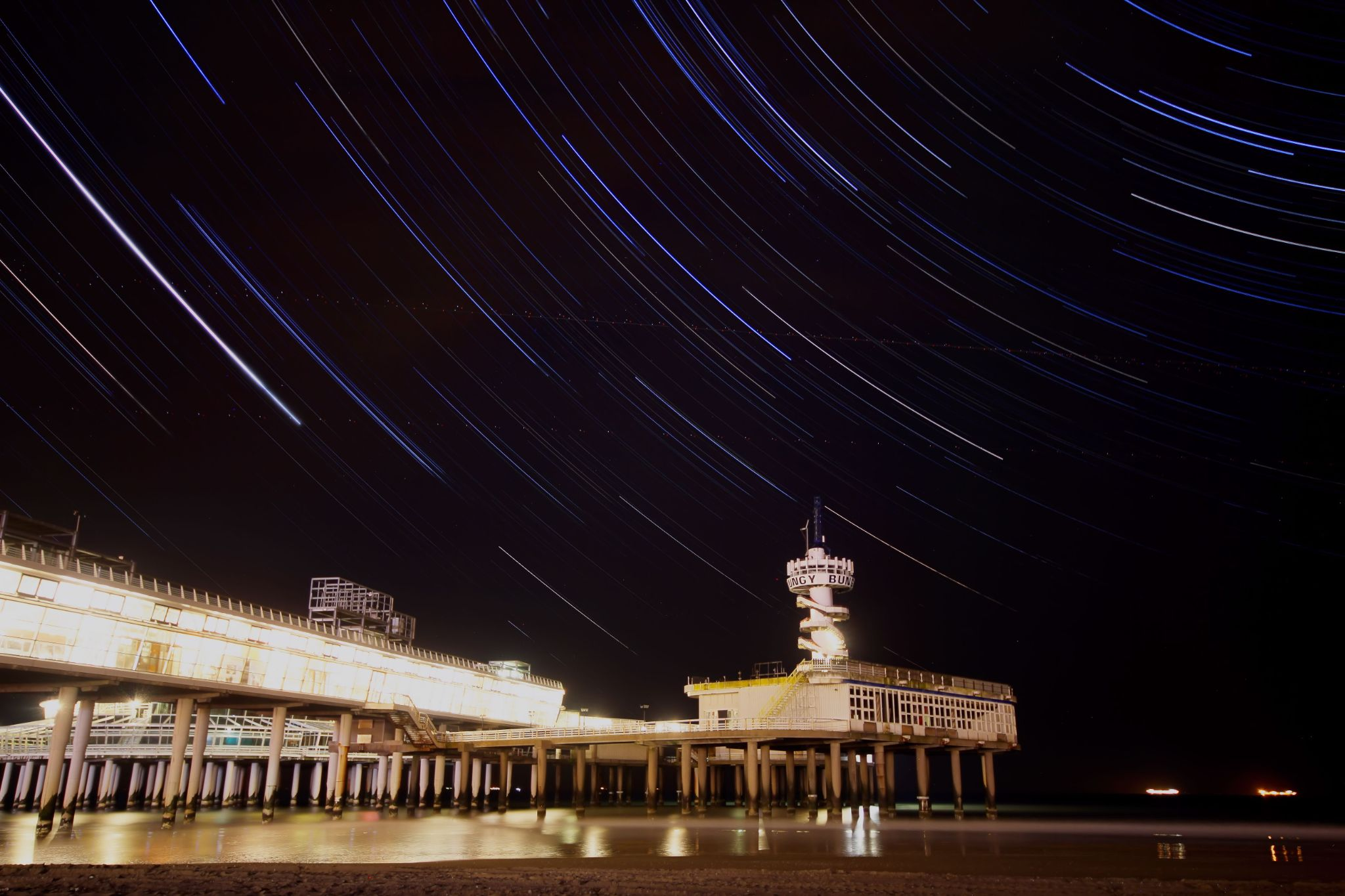 Star trails above city pier by jooud