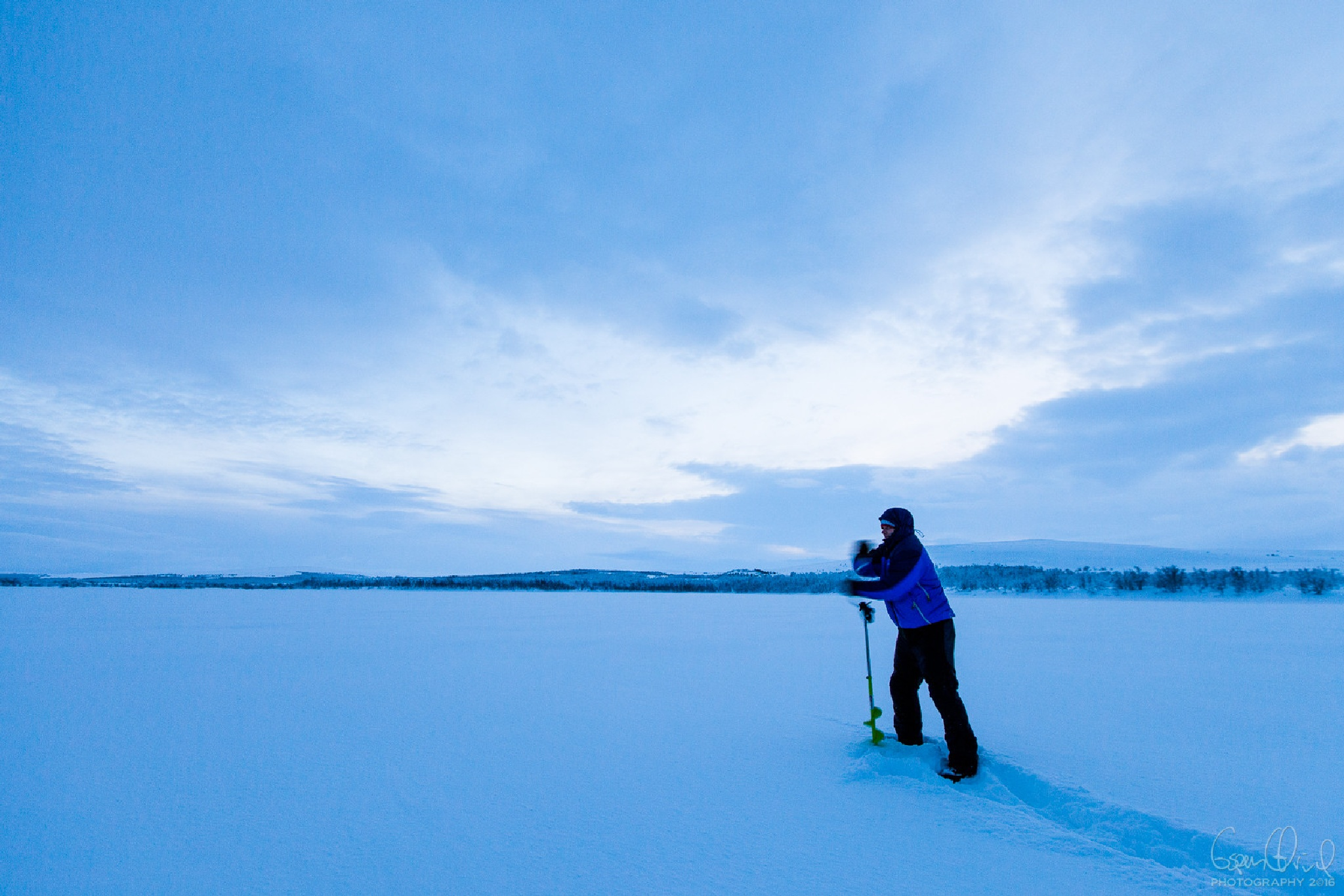 Drilling a hole in the ice by Espen Ørud