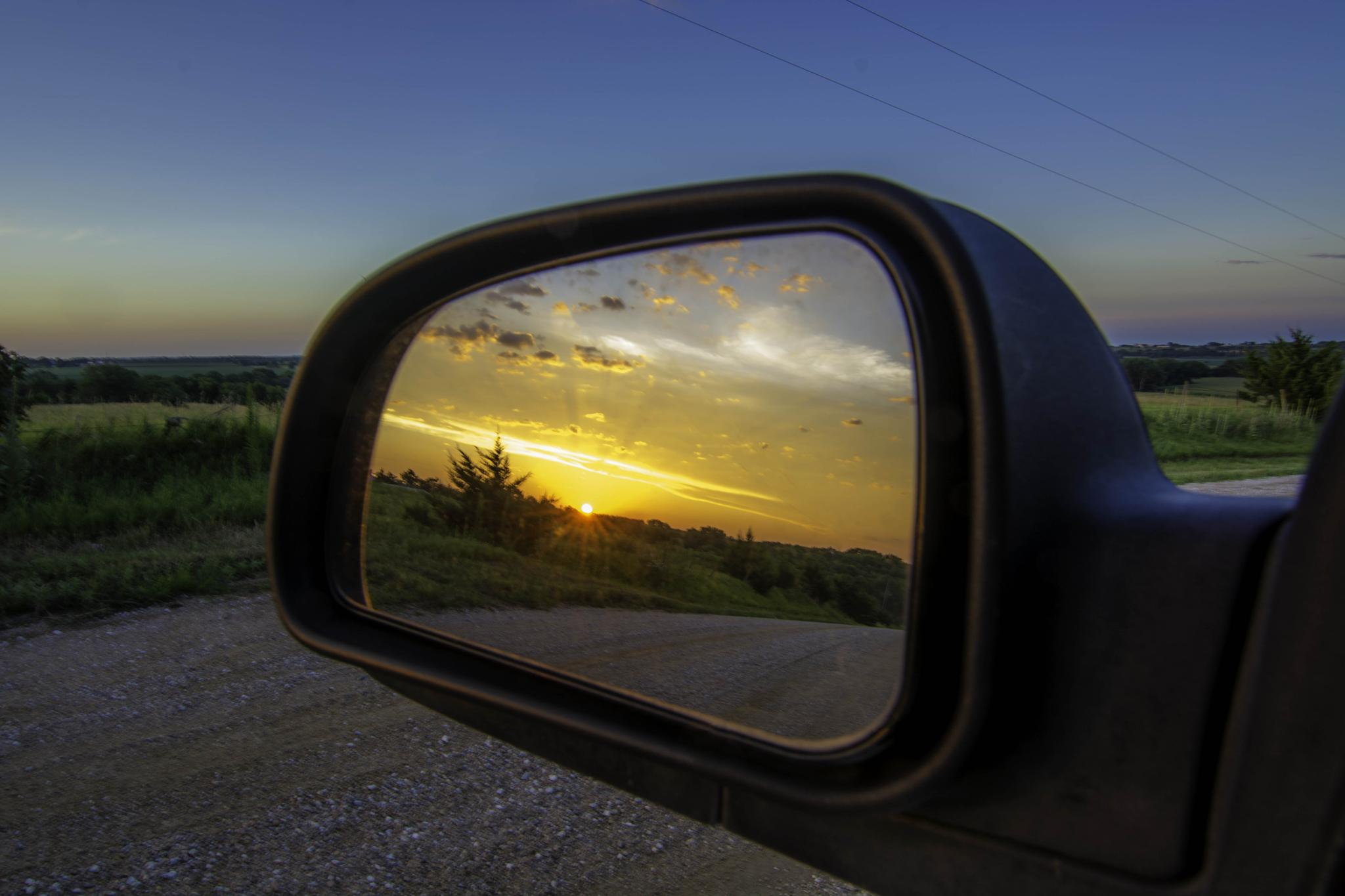 Sunset in the rearview mirror by Jay Douglass