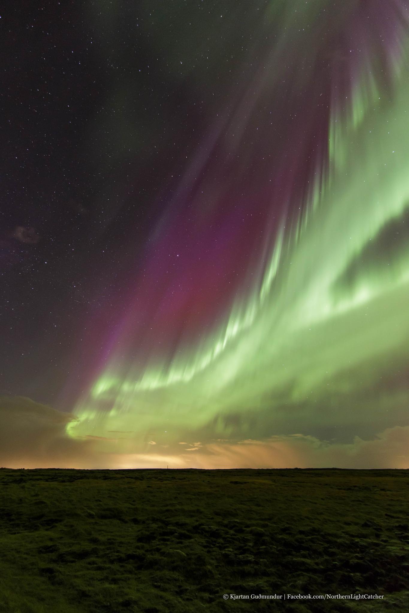 Aurora Blast over mossy field. by Kjartan Gudmundur Juliusson