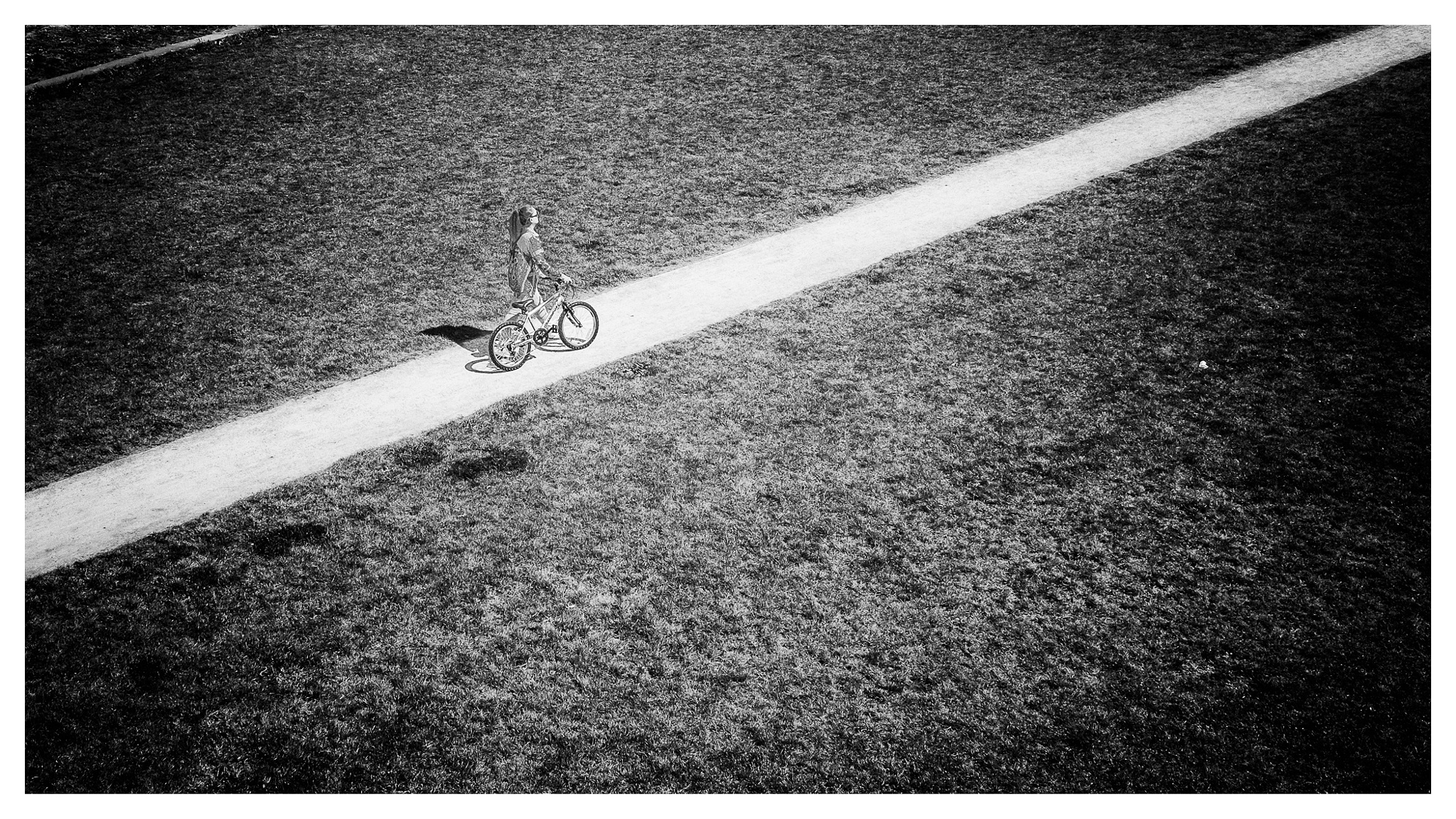 Photo in Black and White #people #street #street photography #monochrome #black&white #girl #antwerp #flanders #belgium #park #park spoor noord #bicycle #path #grass