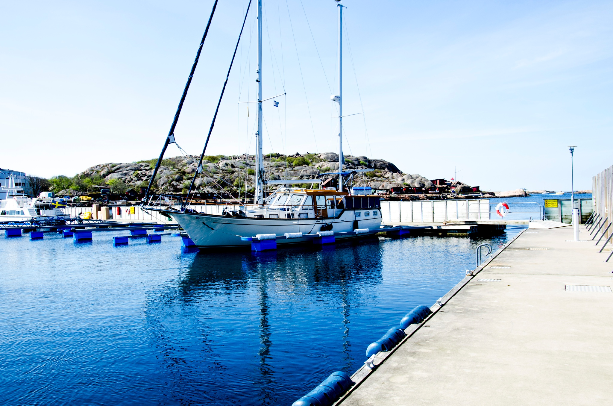 Motor sailboat at the dock by Johnny Lythell