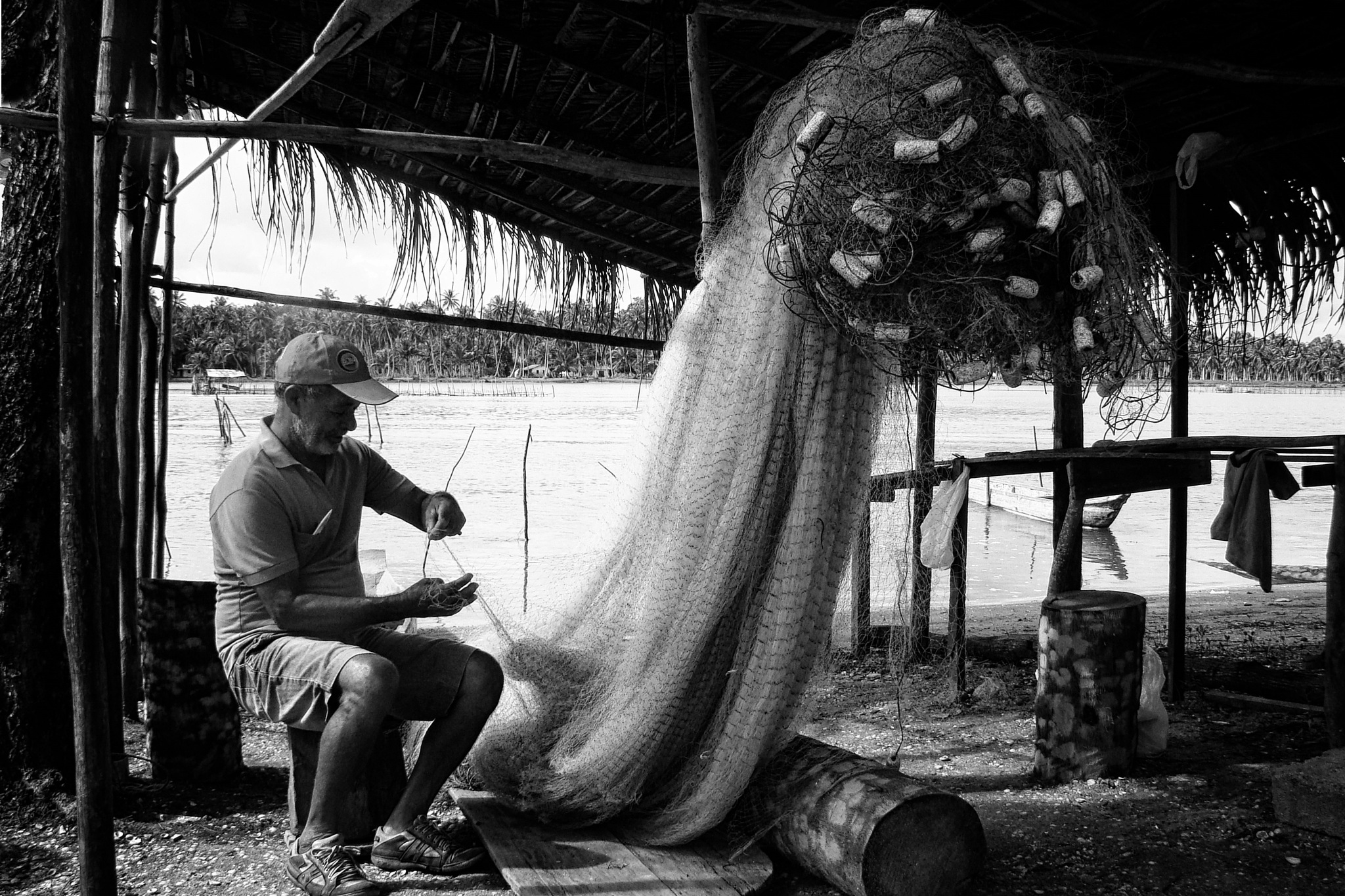Fisherman repairing the net by Fred Matos