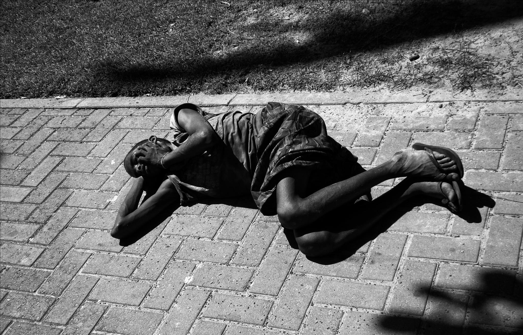 stoned boy sleeping on the sidewalk by Fred Matos