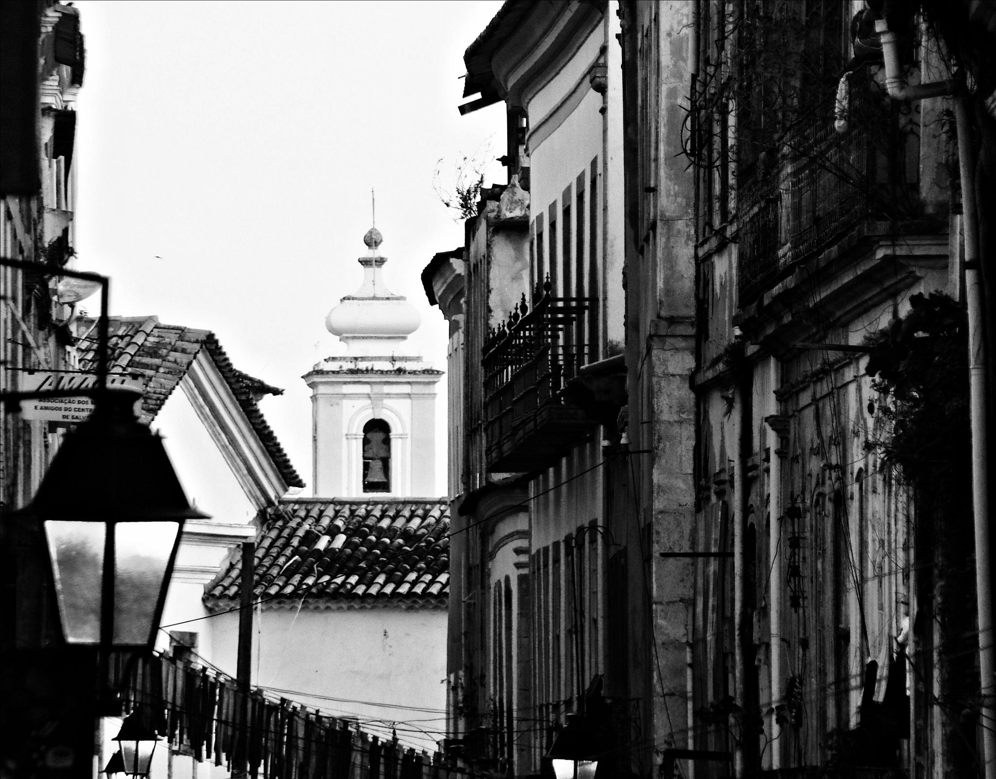 corredor de pardieiros com torre de igreja ao fundo by Fred Matos