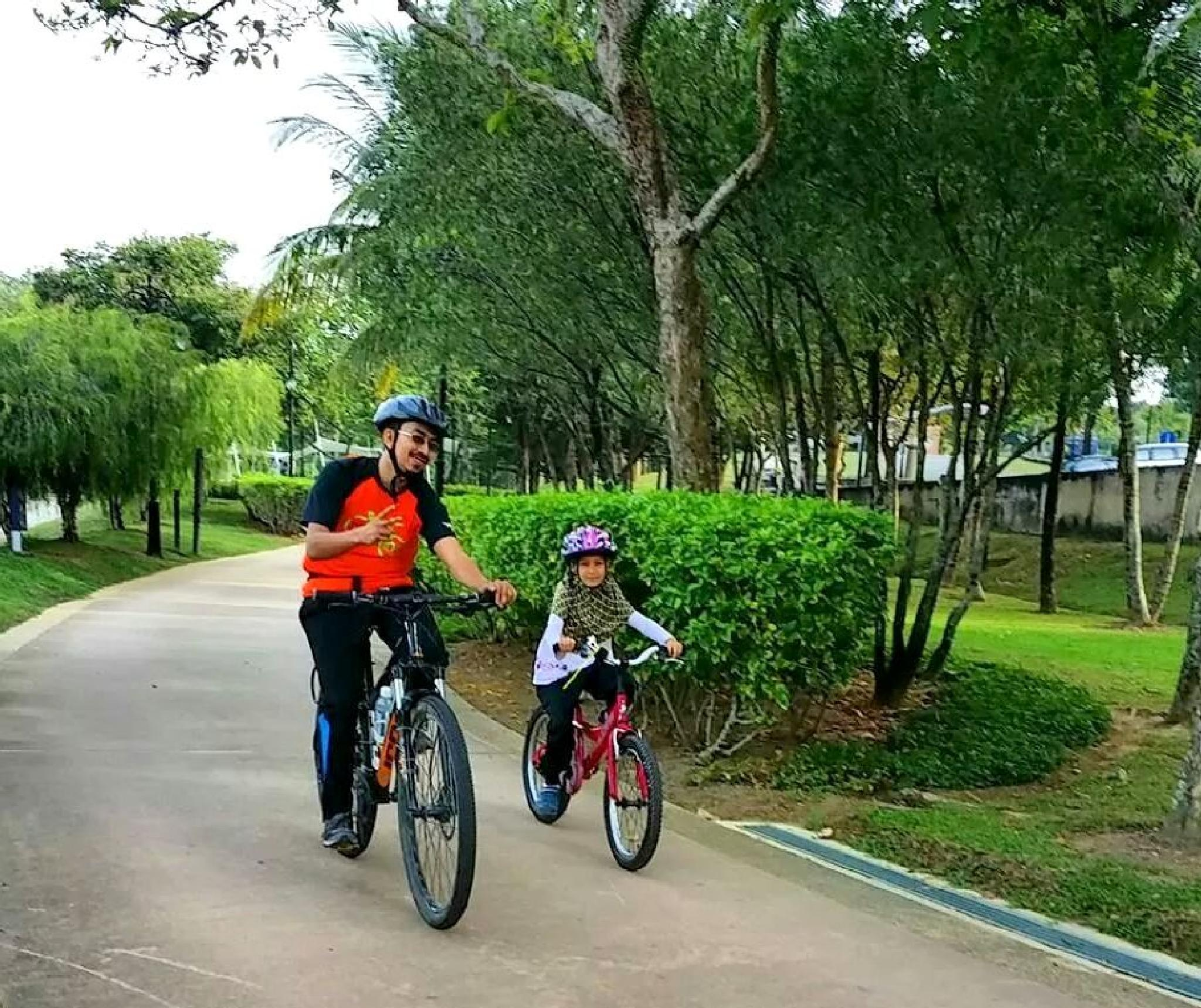 Father and daughter cycling  by Adib Noh