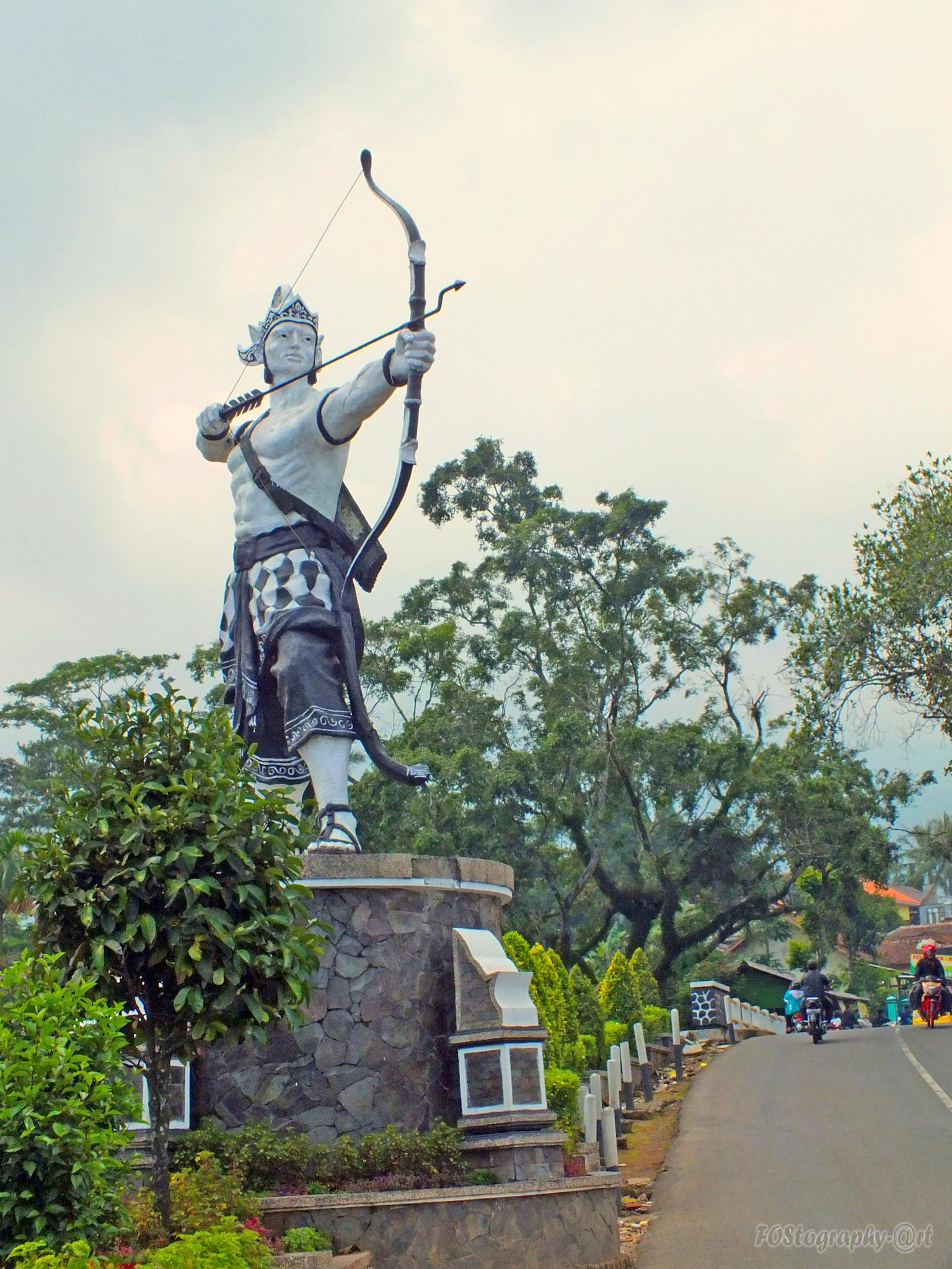 A statue being archery on the roadside by Firman OS