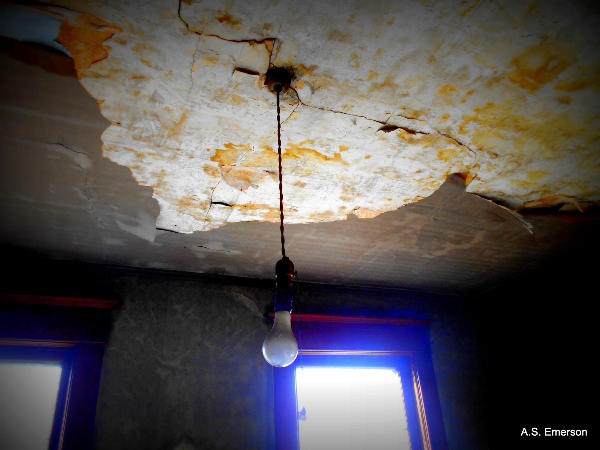 Hanging Light Bulb in Abandoned House by Amy Emerson