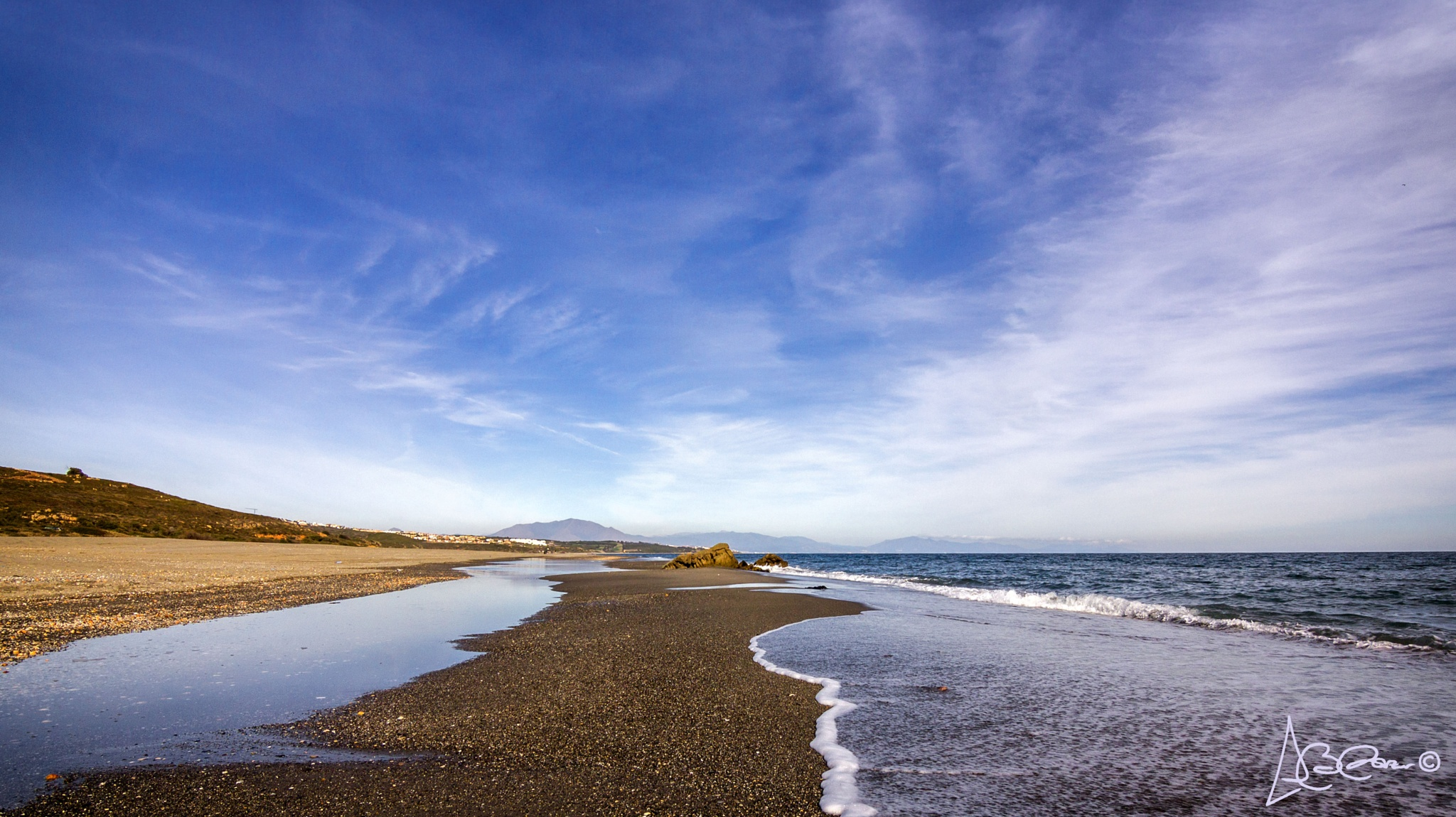 Symmetry between clouds and water (waves) by Antonio Benítez Paz