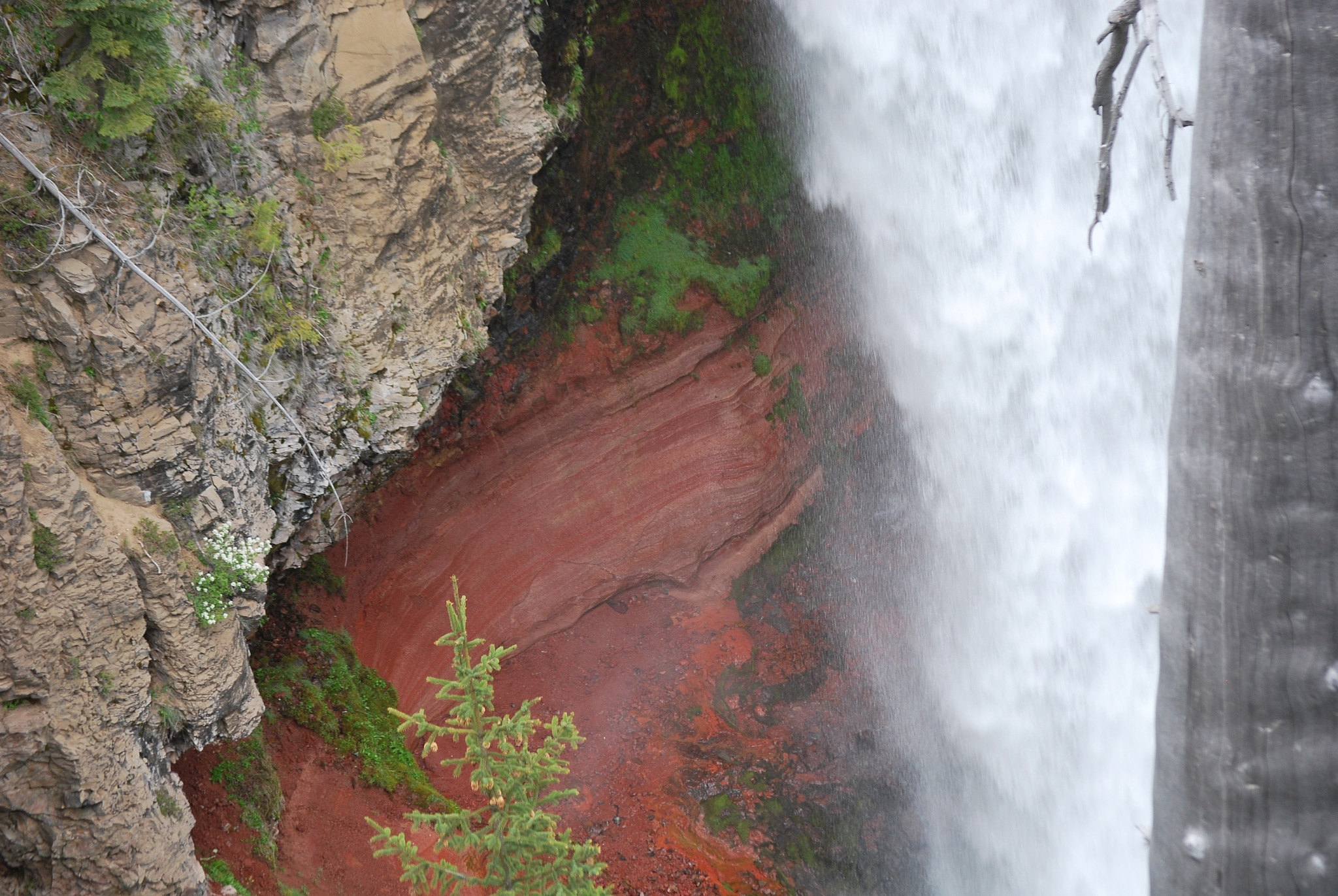 The sedimentary rock wall behind the falls by marilyn wirtz