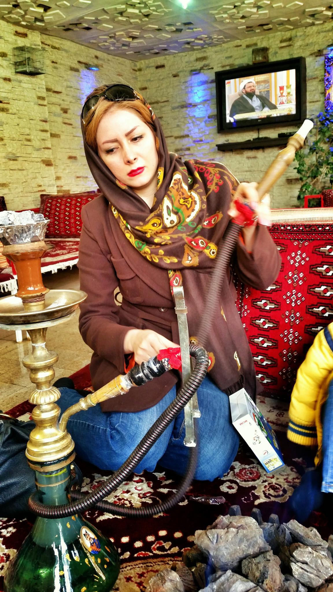 Iranian woman smoking a waterpipe in Darband, Tehran, Iran.  by Henry Kolder