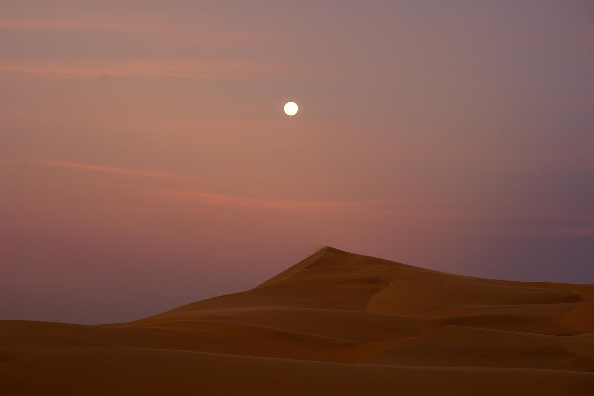 Last rays of sun and moon rises over dunes by Harrold Page