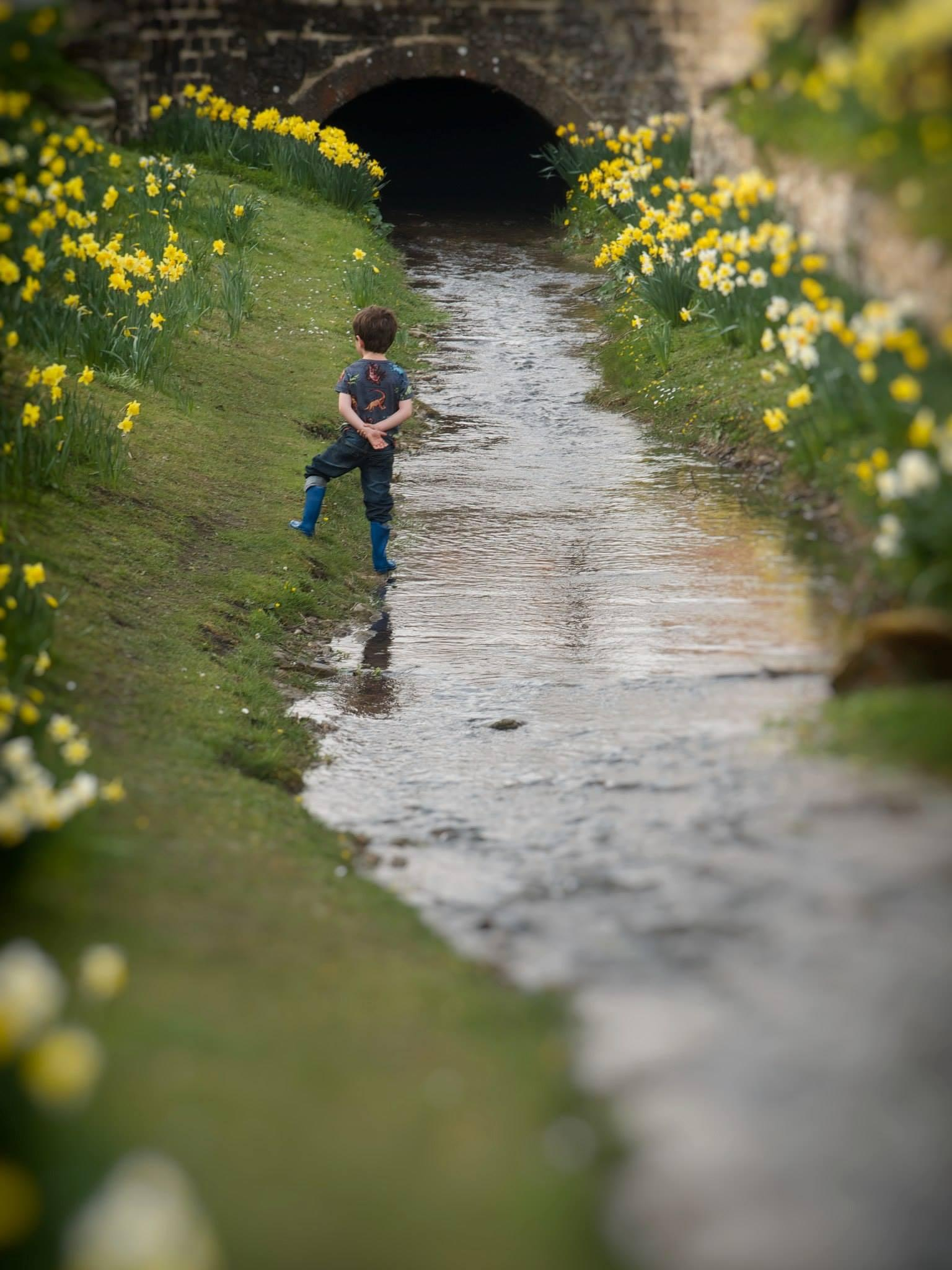 Boy in stream by Jacqui Adams