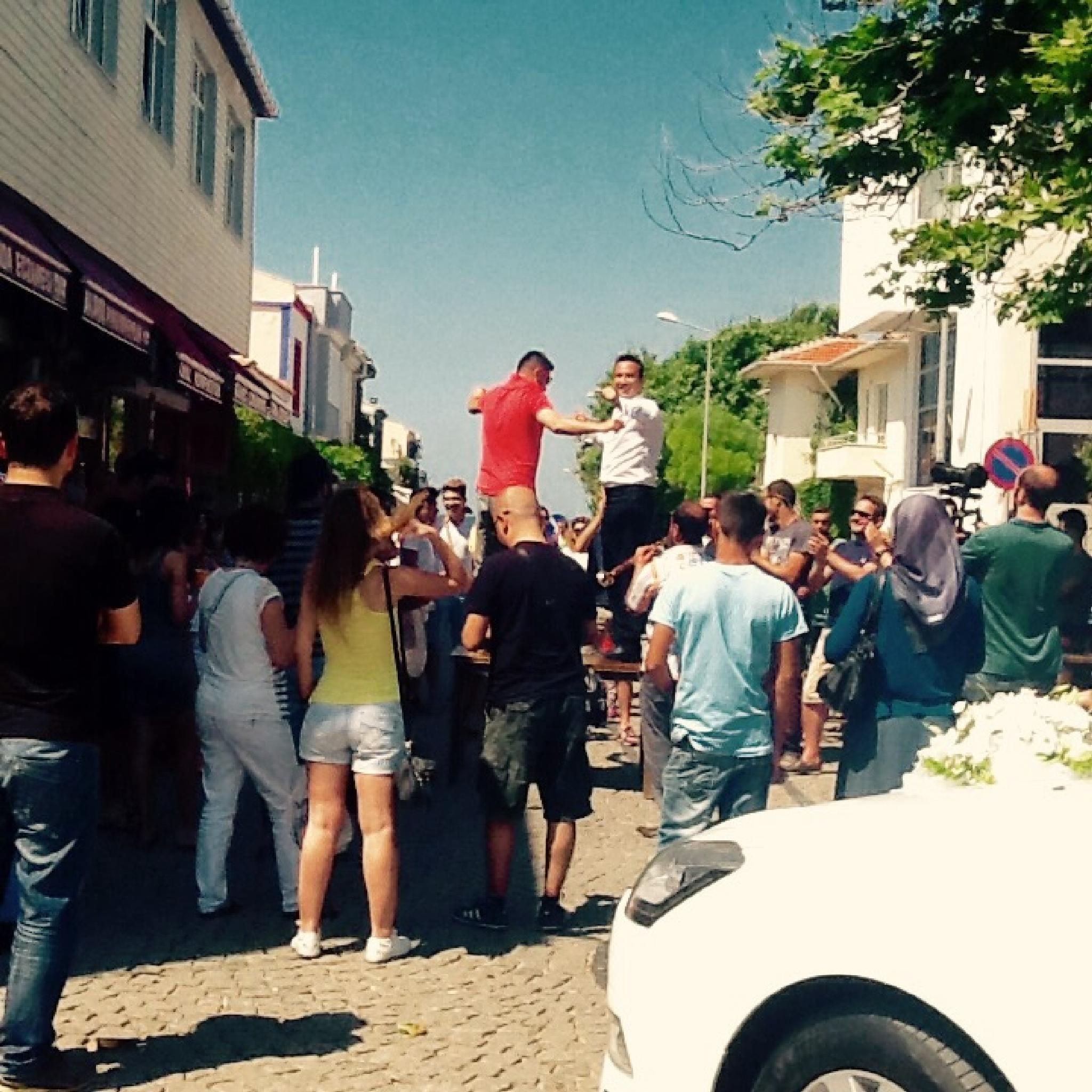 Dancing groom in the street before wedding in Bozcaada by Meriç Aksu