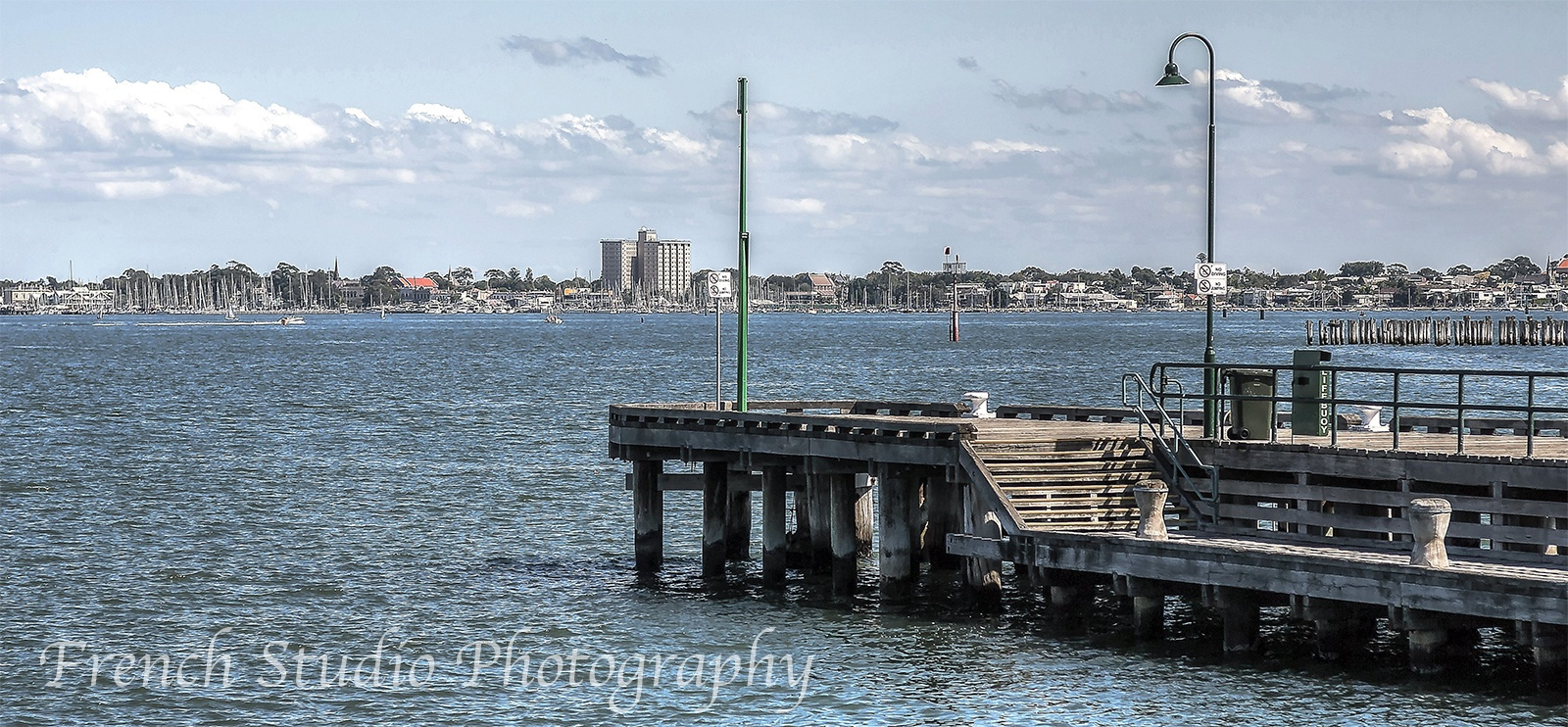 Photo in Random #jetty #water #timber #city #clouds #blue #sky