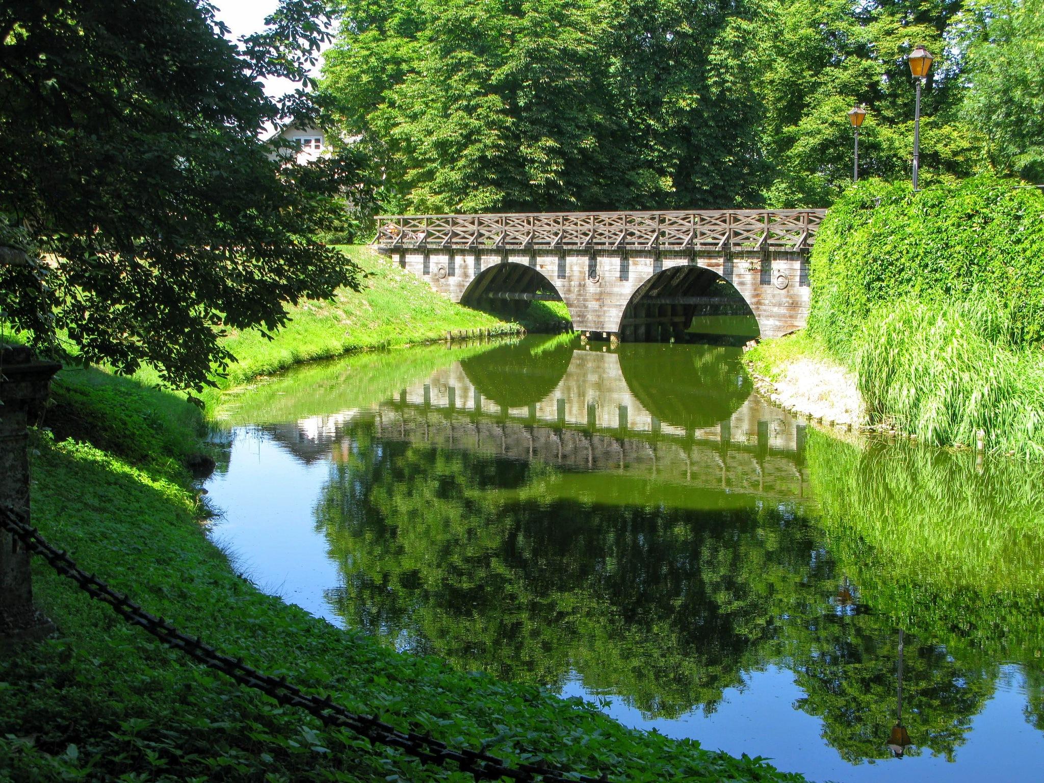 A wooden bridge over a moat by Ela Gajowska