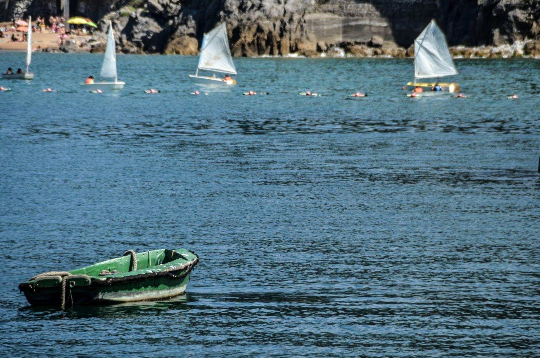 Barca verde contemplando a veleros que compiten by juanalopez
