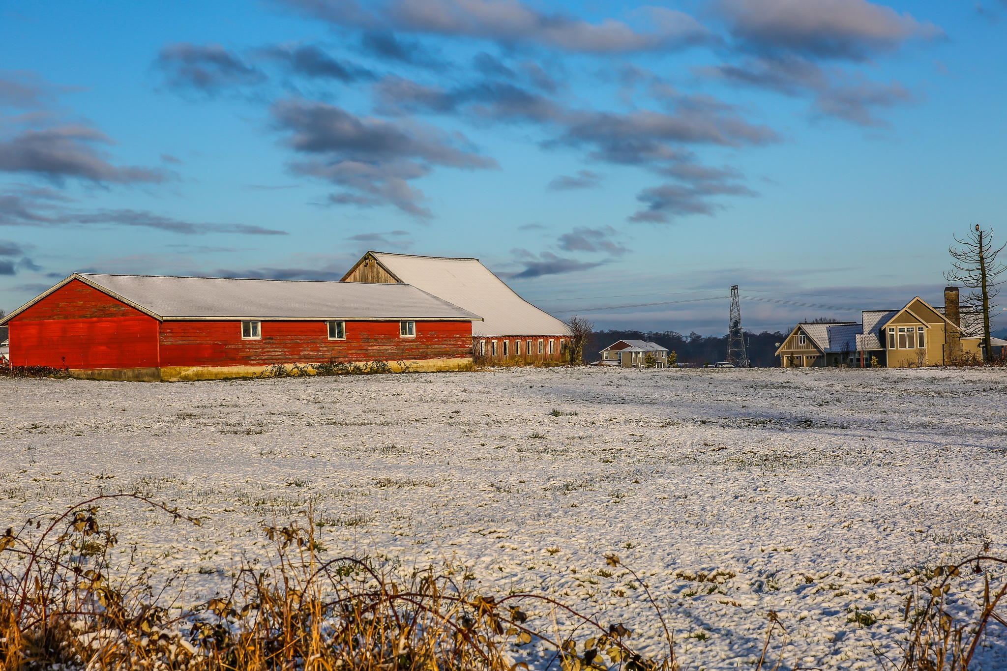 Red barn in a field of snow by Mark Joseph