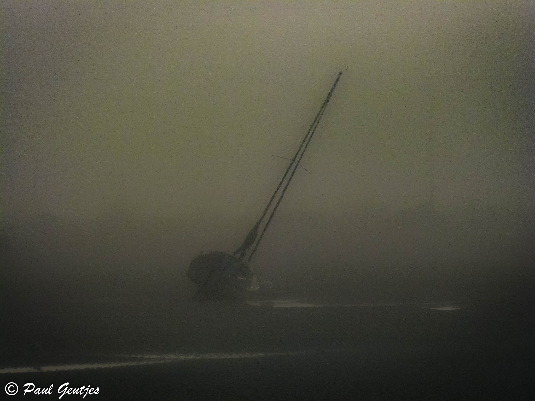 Sailing boats stuck in low tide and in the fog. Serie 4 of 8 by Paul Geutjes
