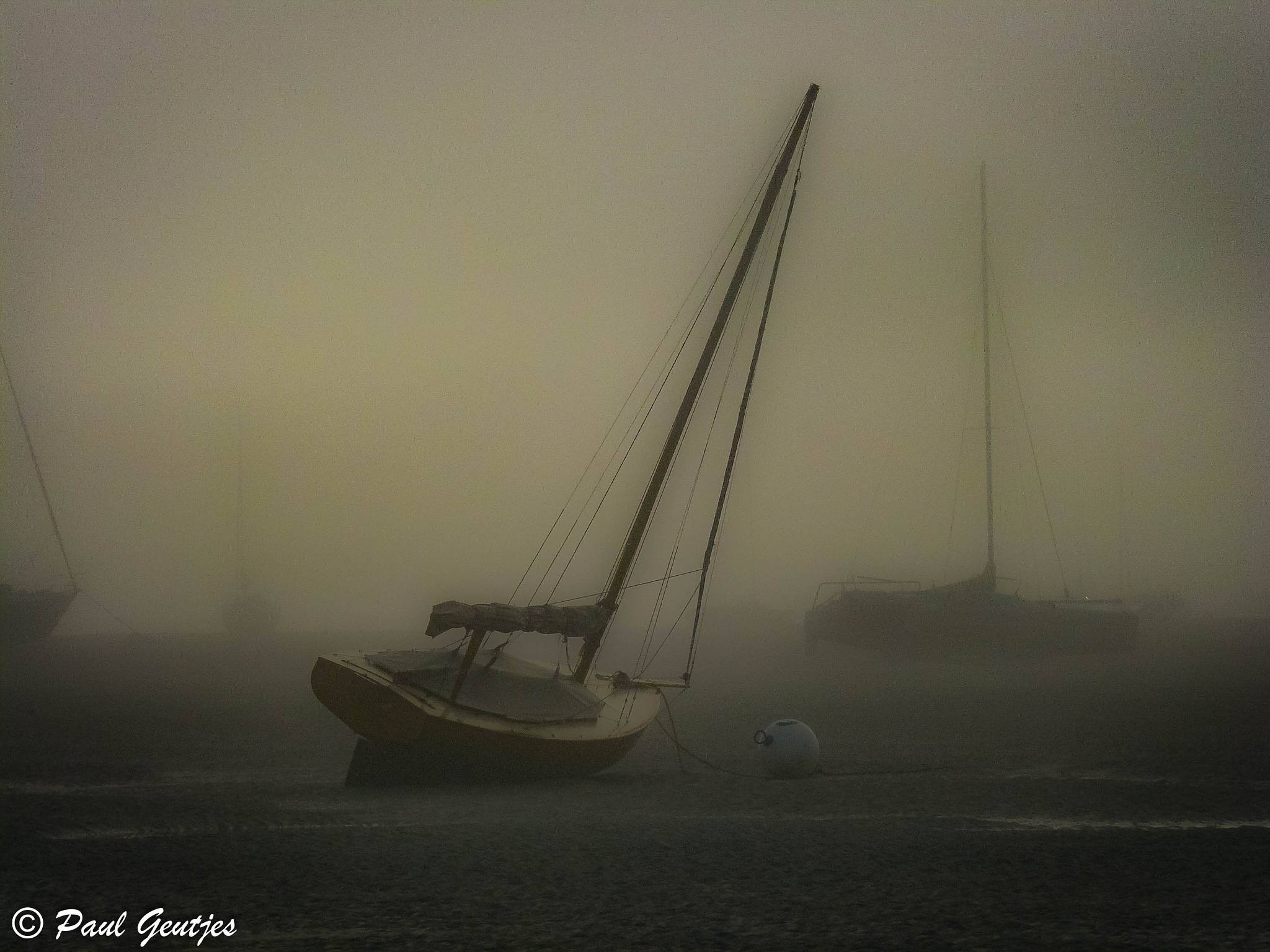 Sailing boats stuck in low tide and in the fog. Serie 6 of 8 by Paul Geutjes