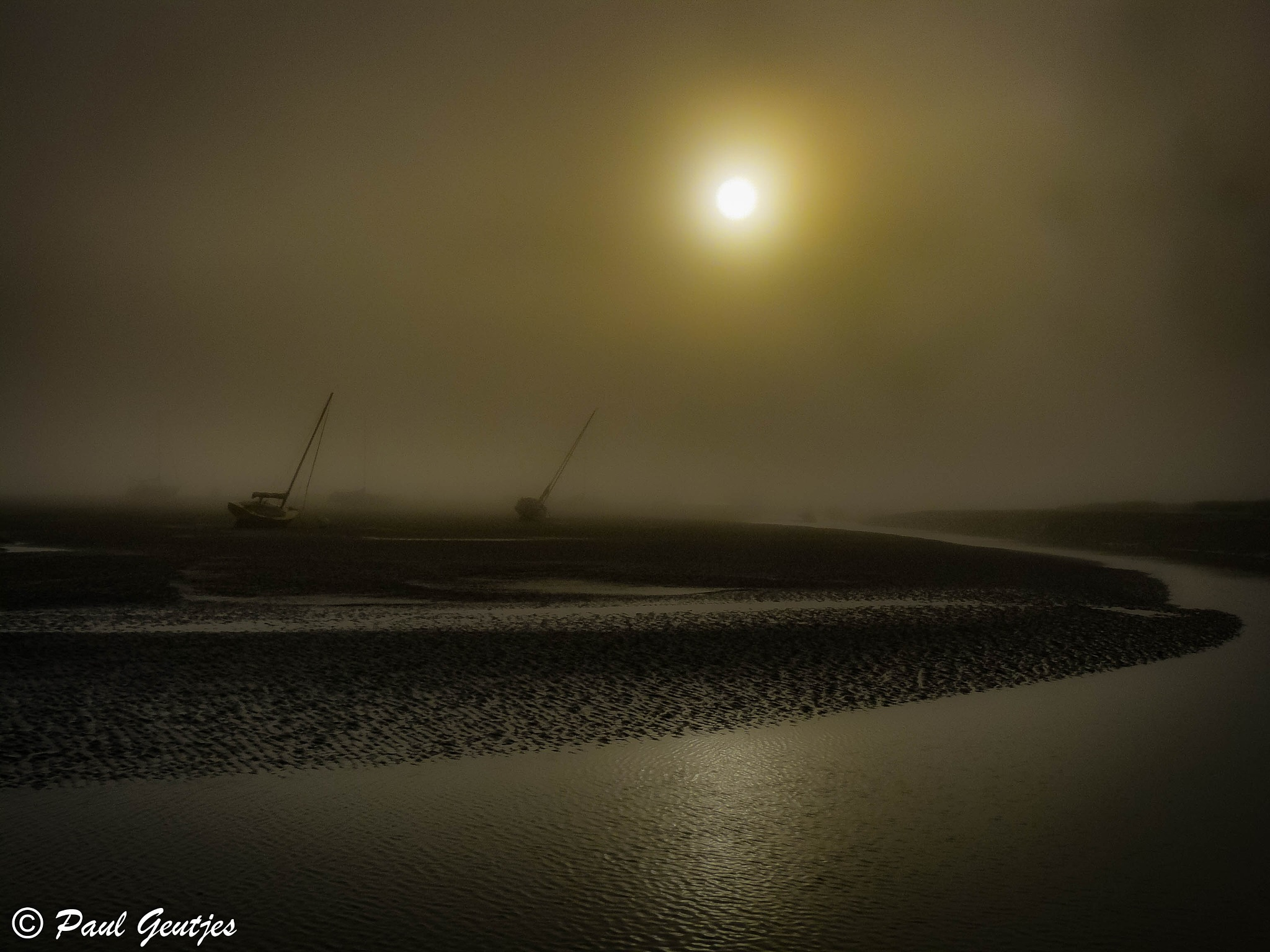Sailing boats stuck in low tide and in the fog. Serie 5 of 8 by Paul Geutjes