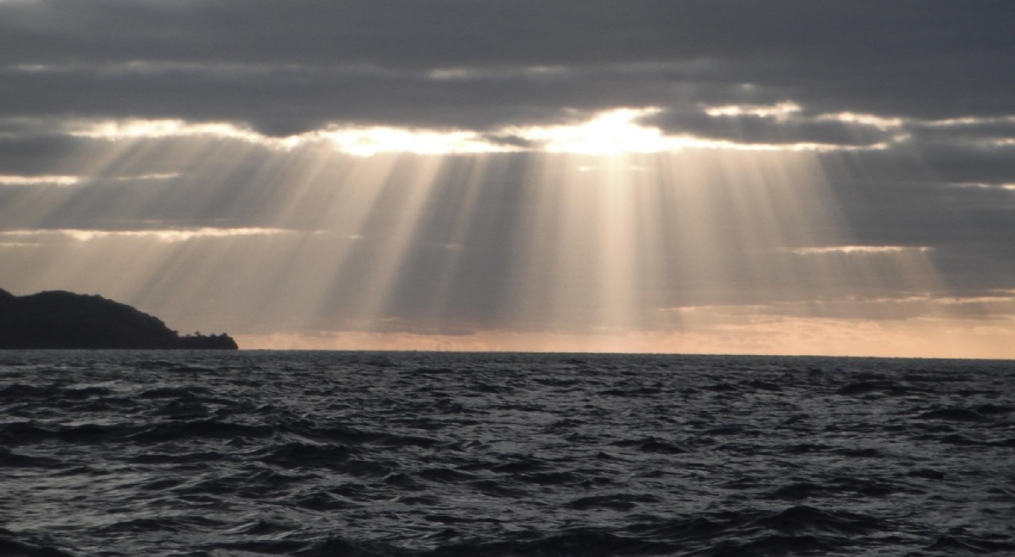Rays beam down to a foreboding sea by johndflatt