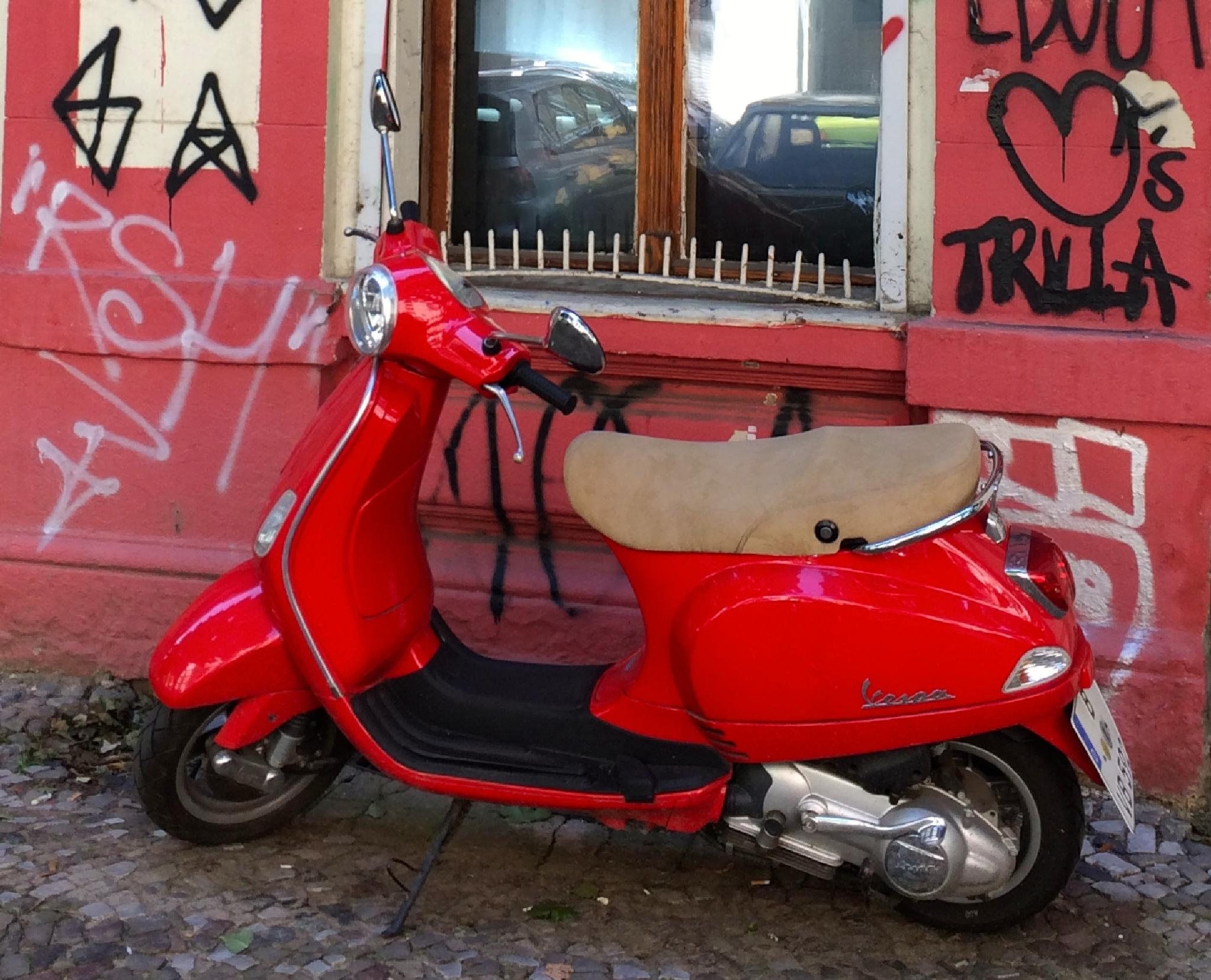 red vespa in front of red house by m.etemadieh
