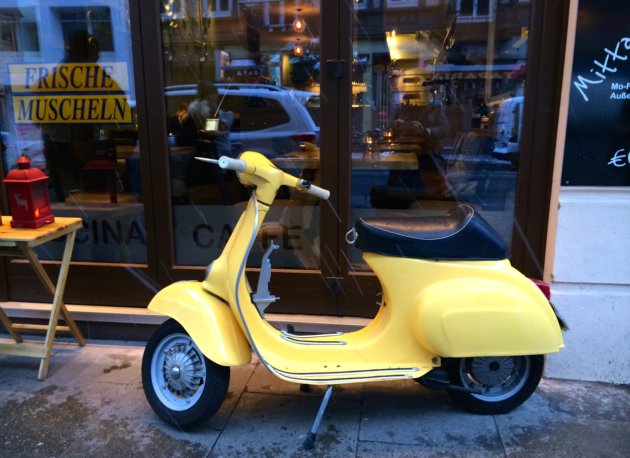 yellow vespa in front of a restaurant by m.etemadieh