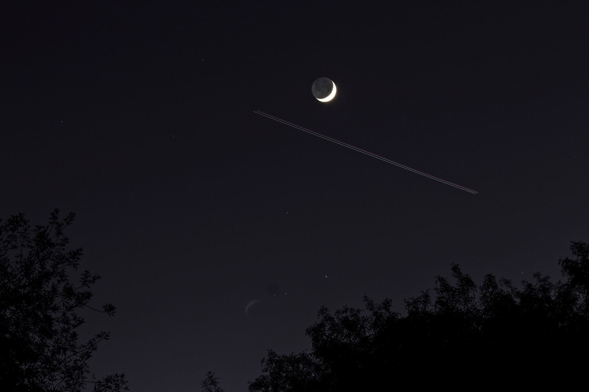 Crescent moon with plane by Wade Pitcher