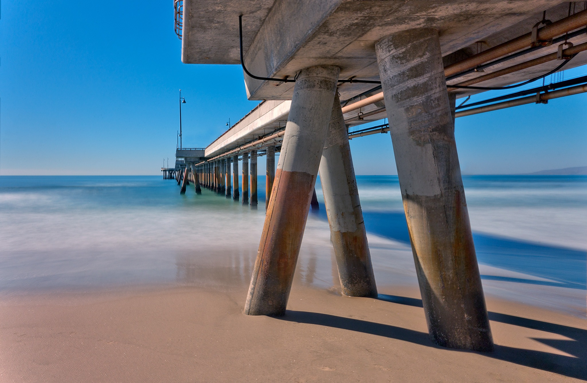 Photo in Sea and Sand #summer #ocean #pacific #waves #water #blue #cyan #foam #sky #clear #pier #architecture #pillars #columns #empty #vivid #vibrant #deserted #californisa #california #los angeles #la #ca