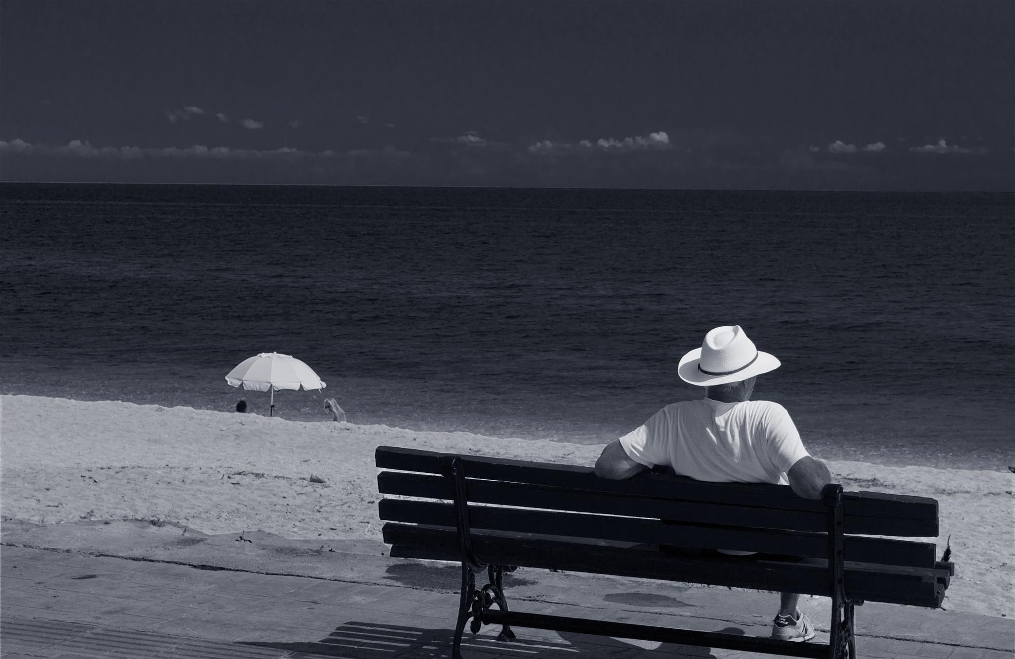 Man with white hat by Agelos Kardamilas