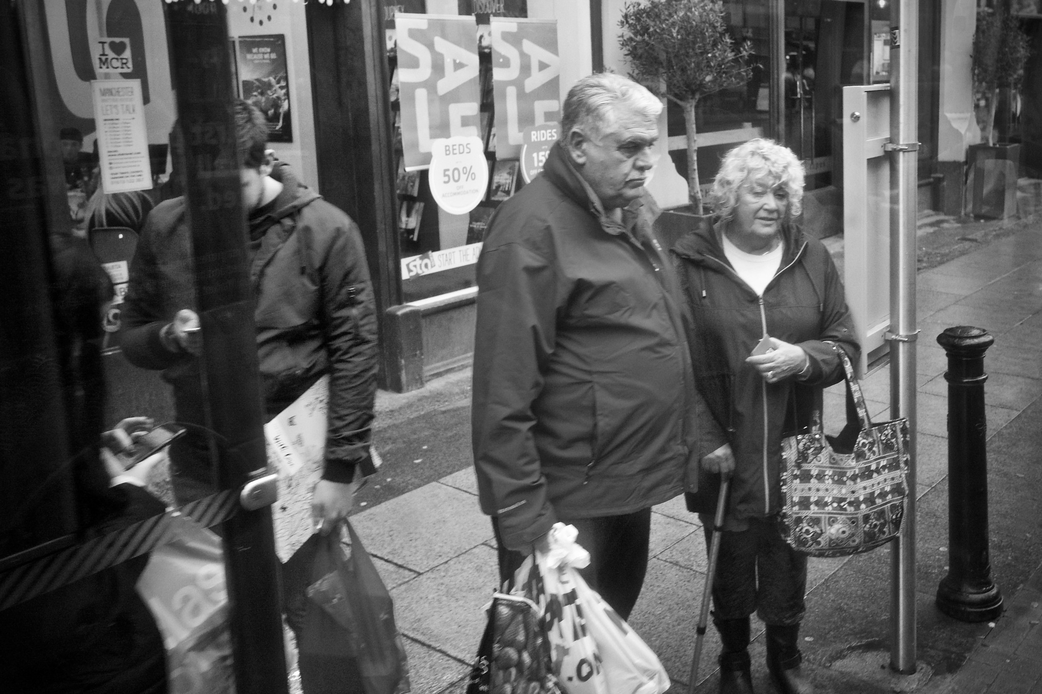 Photo in Street Photography #people #standing #waiting #bus stop #couple #black and white #monochrome #street #street photography #manchester city centre #manchester #uk #urban #deansgate #buildings