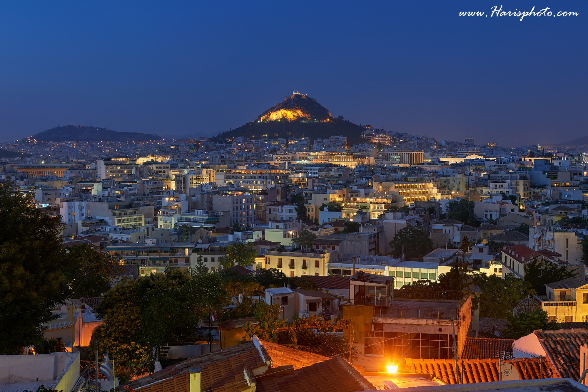 View of Athens dominated by Lycabettus hill. Image taken from Anafiotika in the old Town. by Haris Vithoulkas