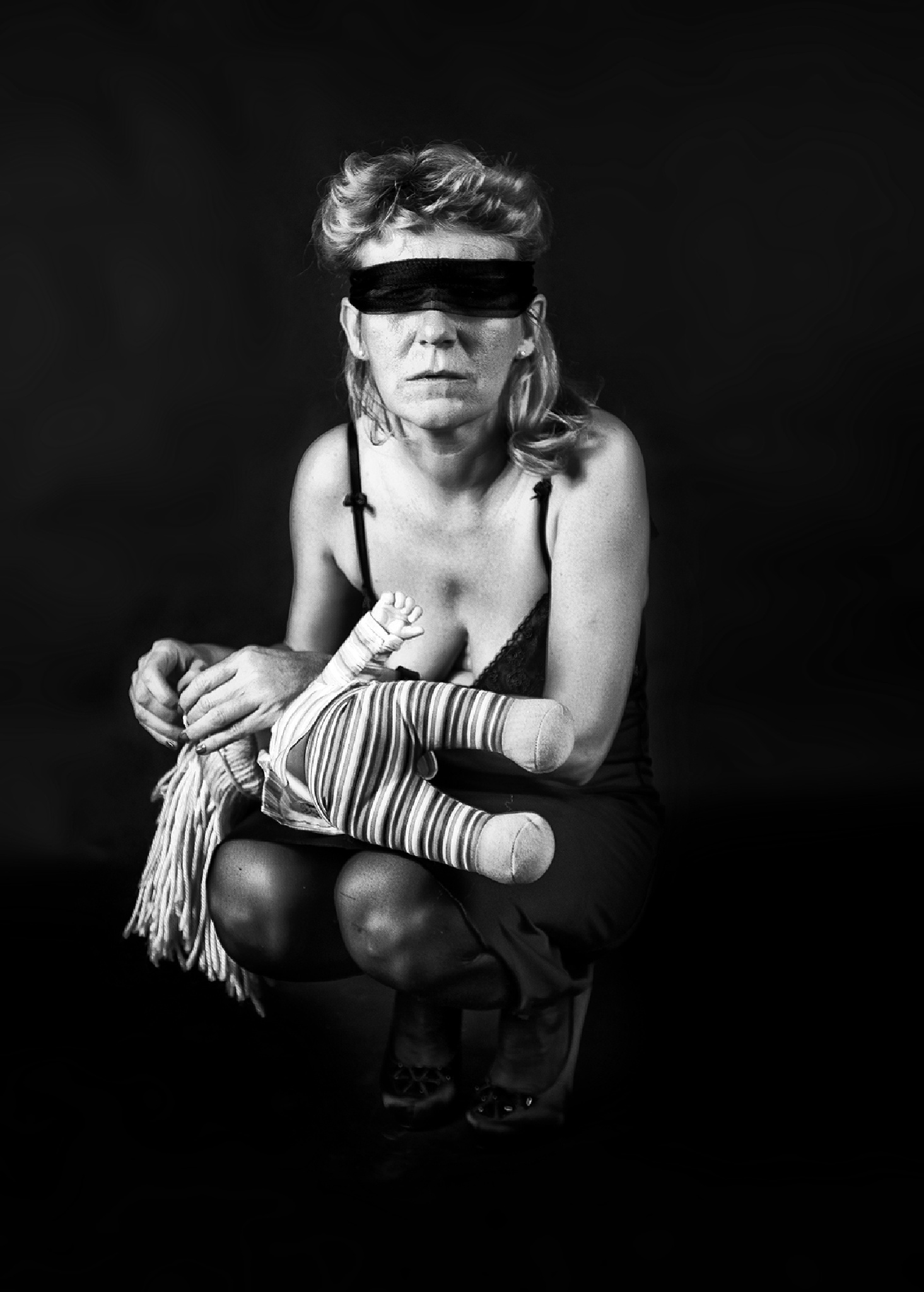 woman with doll blindfolded by Hybryds