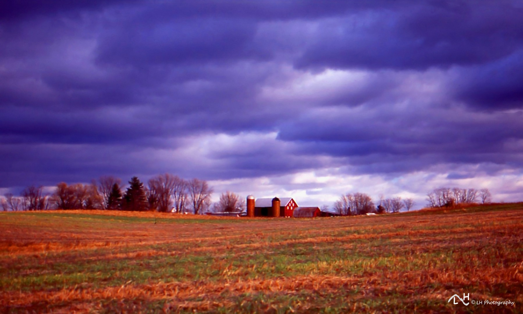 Farm and fields on a stormy fall day by Laurie Heupel