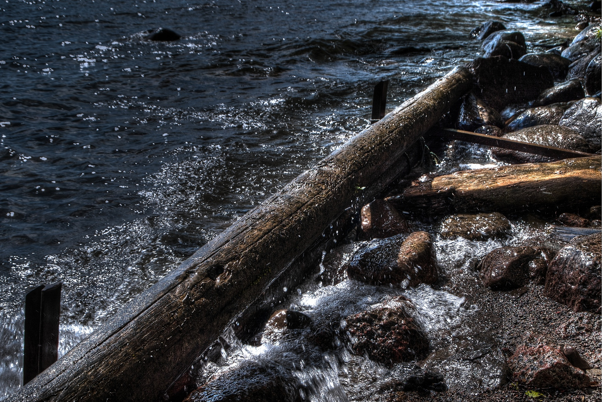 Water splashing on log by Mattias Glimsö