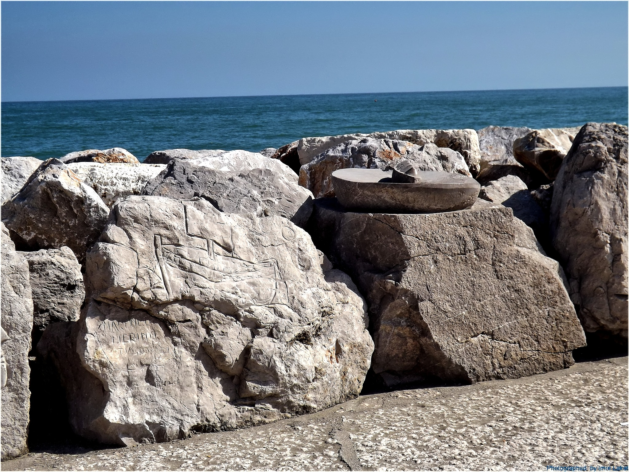 Statues carved in stone ,    Breakwater on the beach in Caorle by Imre Lakat