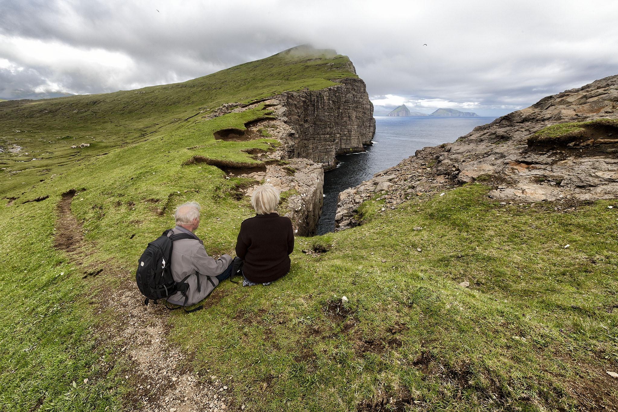 My parents relaxing near Trælanýpa  by Faroe Islands Hiking
