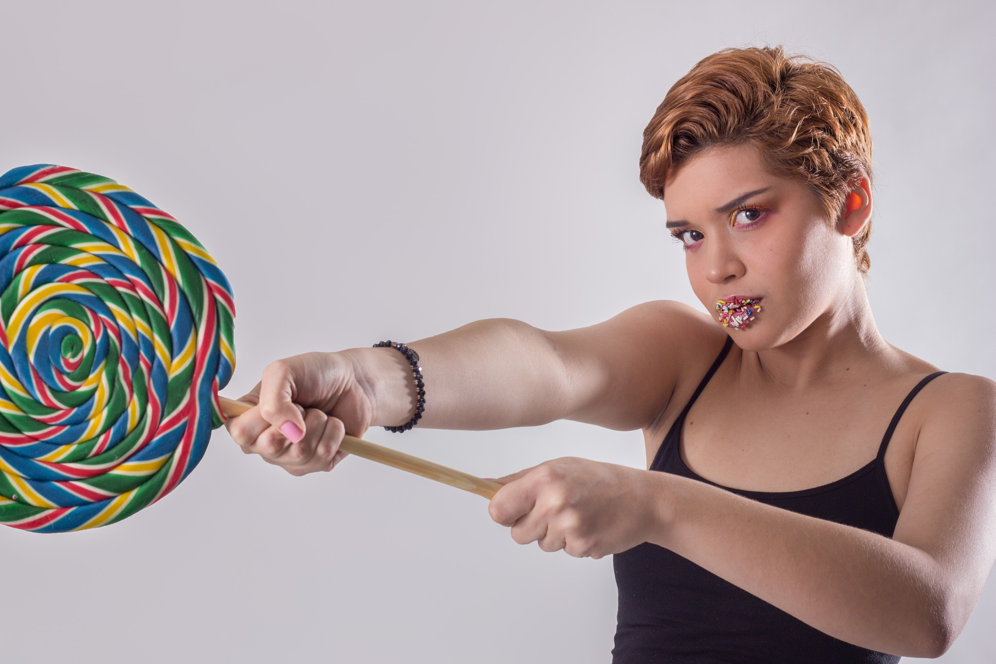Girl using a candy as weapon by Tiago Deliberali Santos