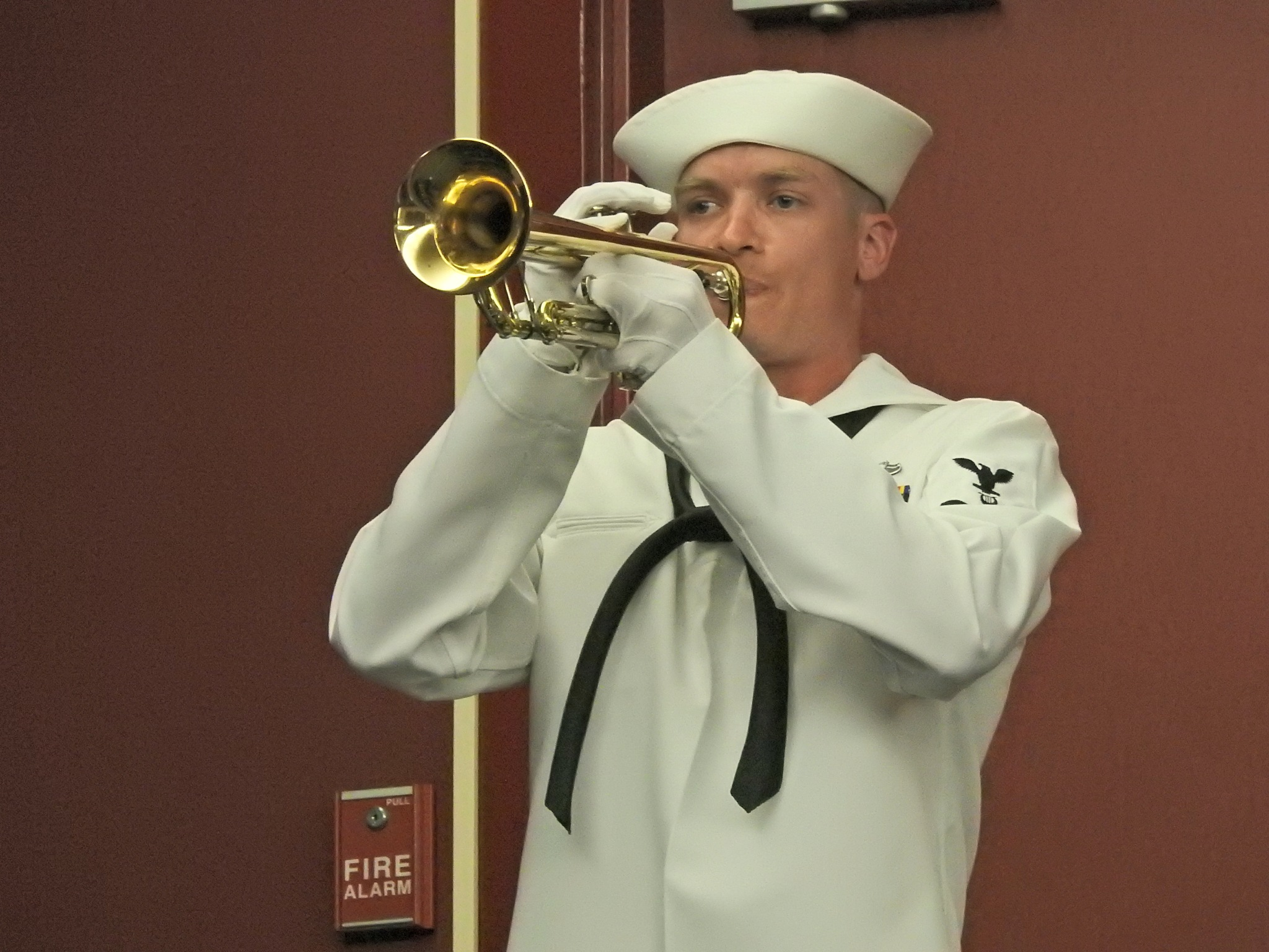 Sailor playing taps by Mat Manes