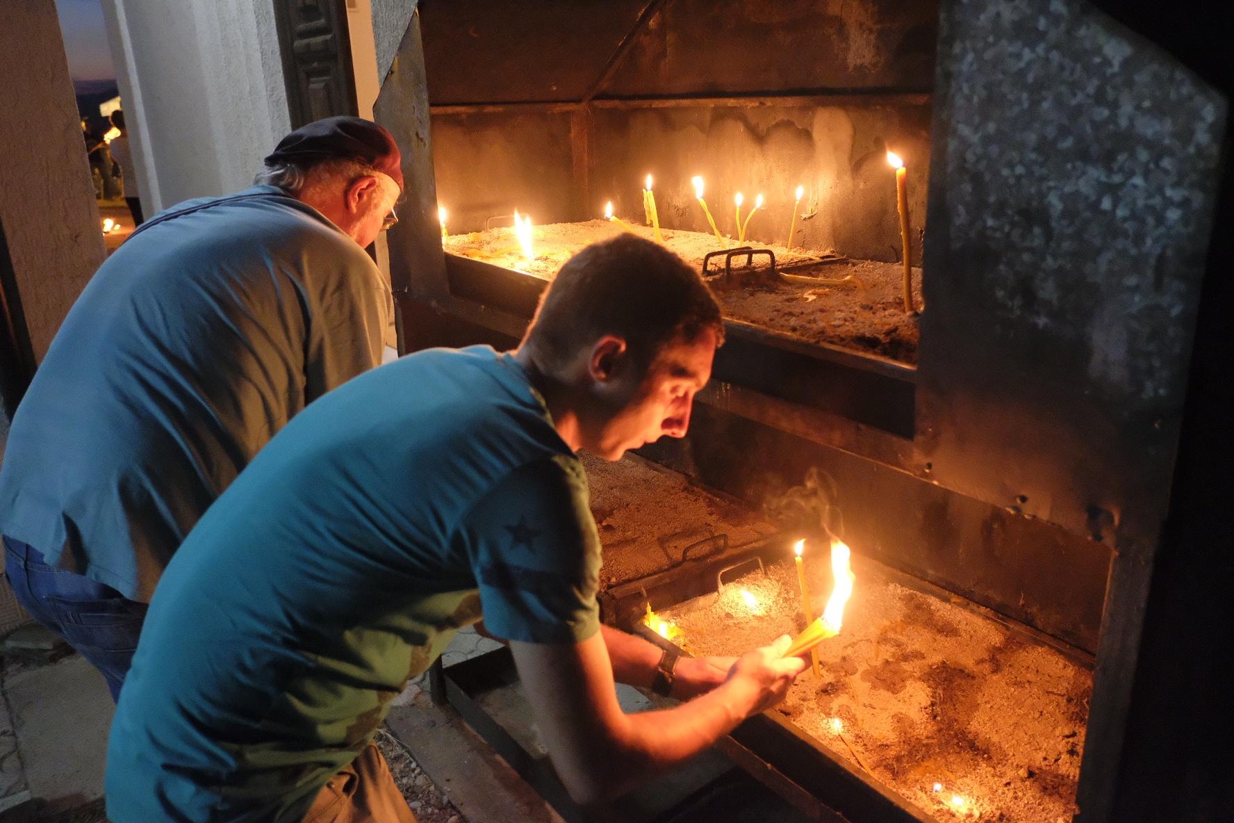 Ortodox Serbs light candles in the church by Goran Jorganovich