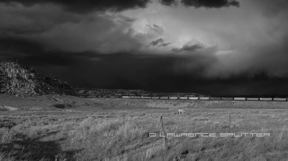 A train travels into approaching storm by Lawrence Splitter