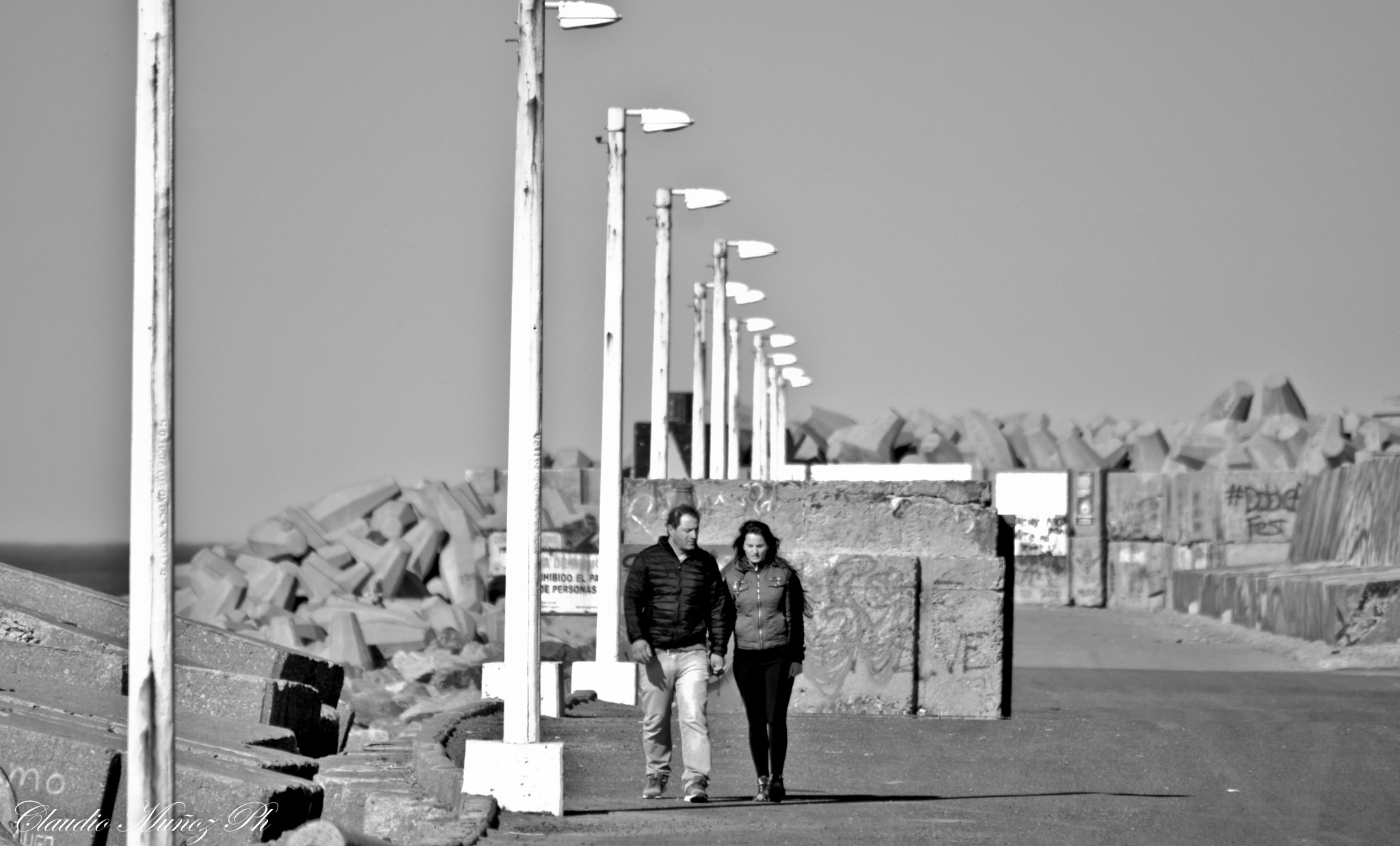 Walking on the riprap by Claudio Muñoz