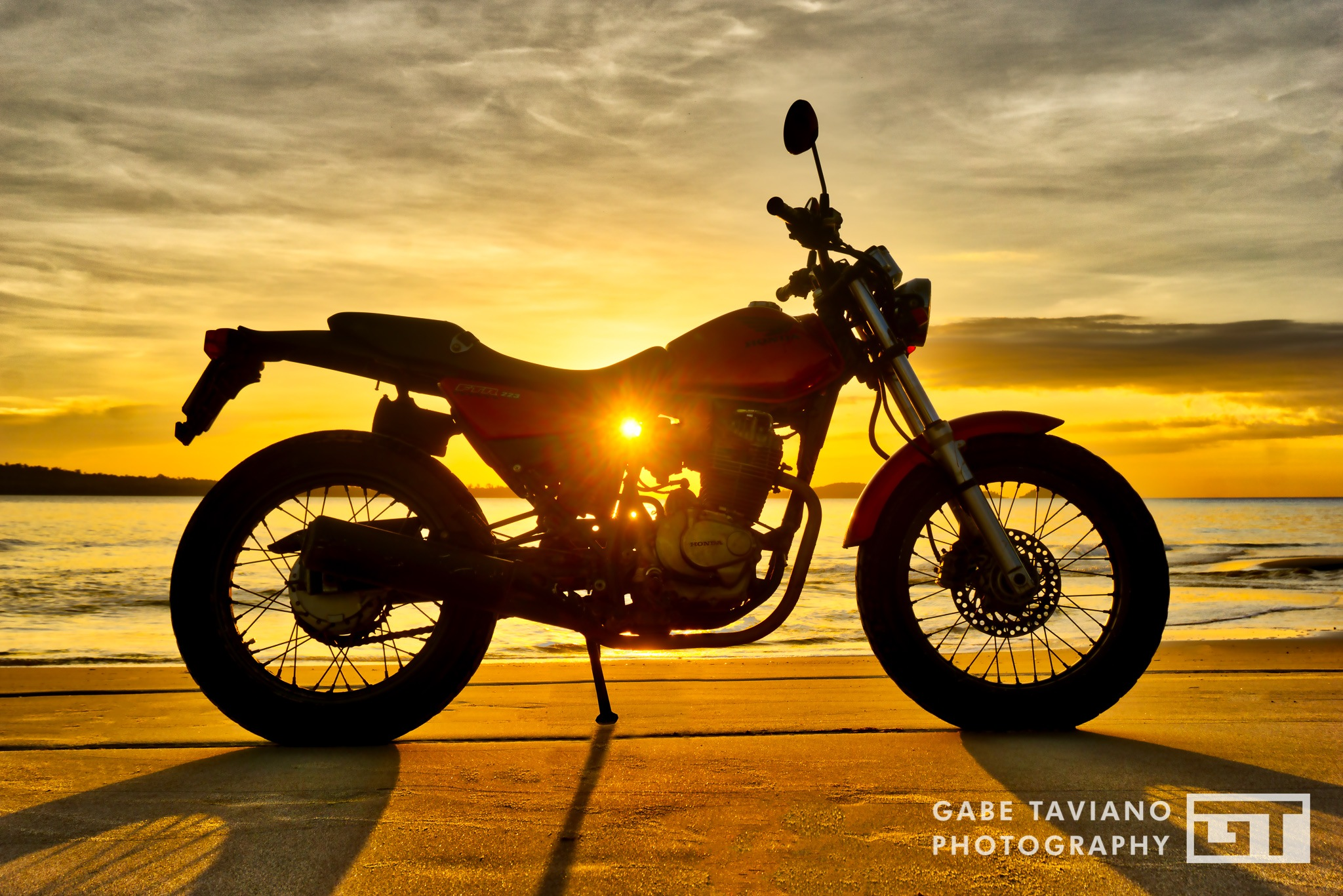 Motorcycle silhouette at sunset on the beach by Gabe Taviano