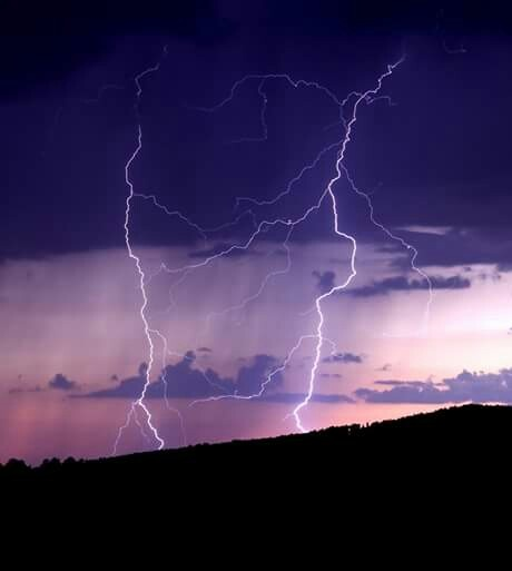 Lightning in the sunset by Chade Woodard