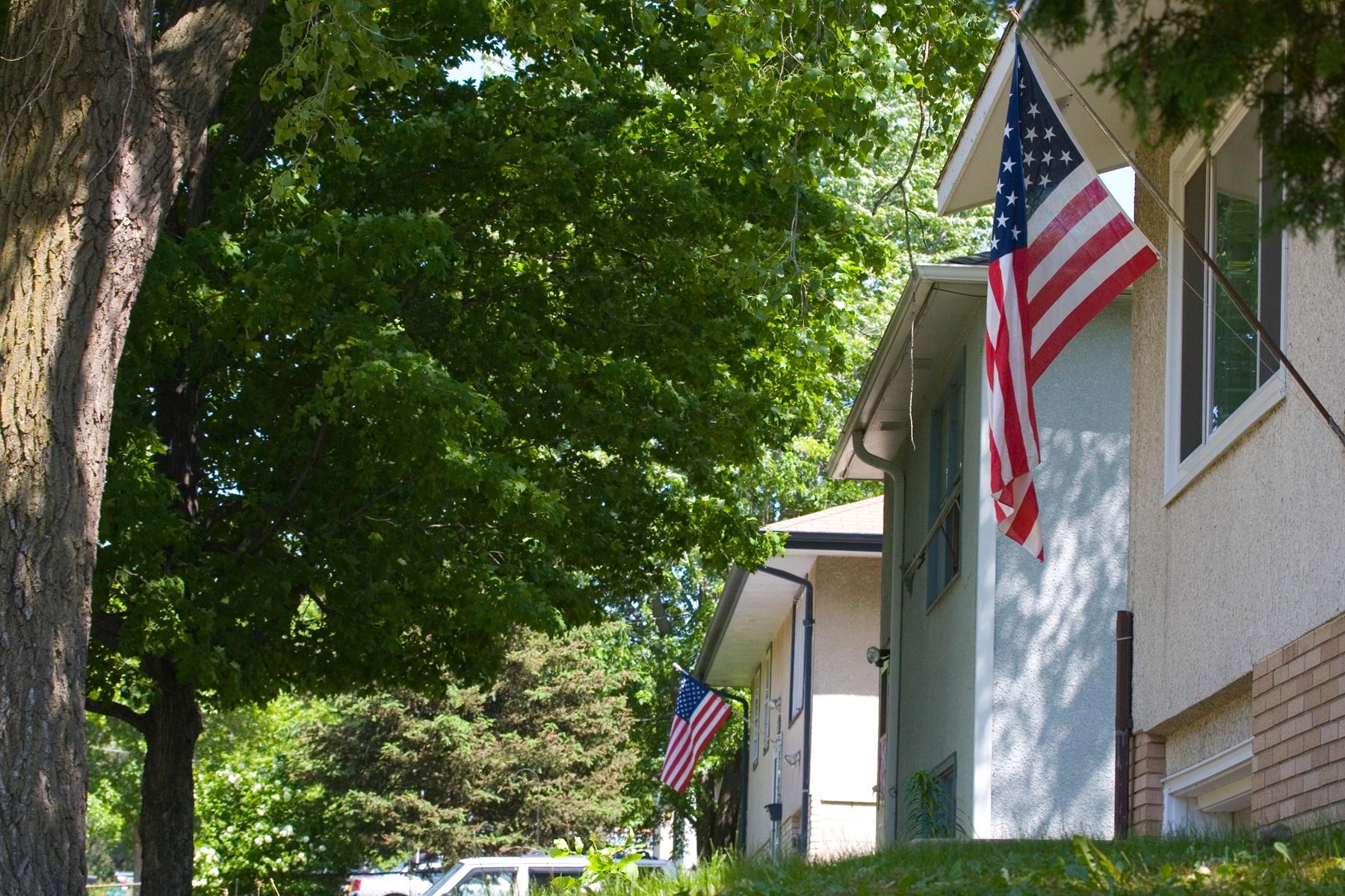 US flags on houses by Bernard Mordorski