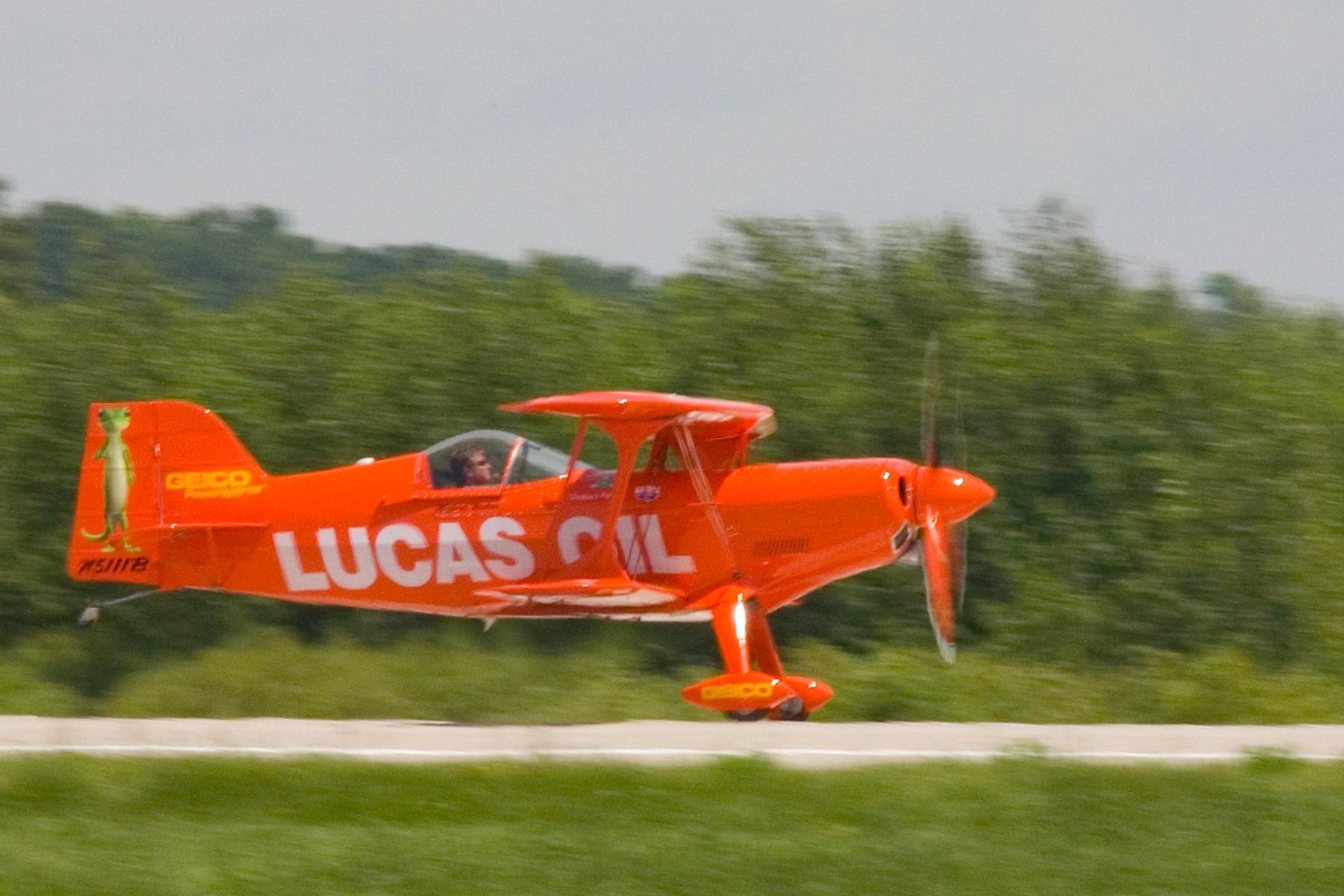 Lucas oil biplane skimming the runway by Bernard Mordorski